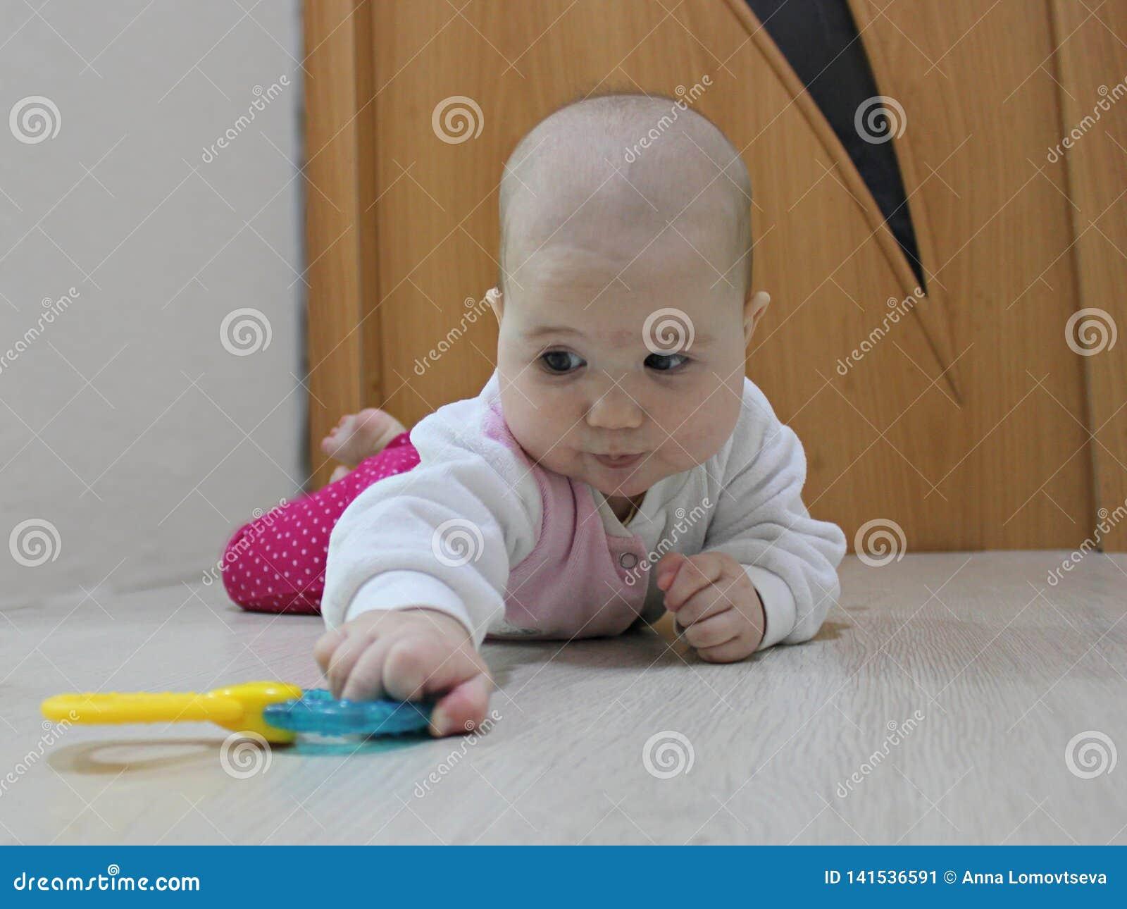 Младенец вползая после игрушки