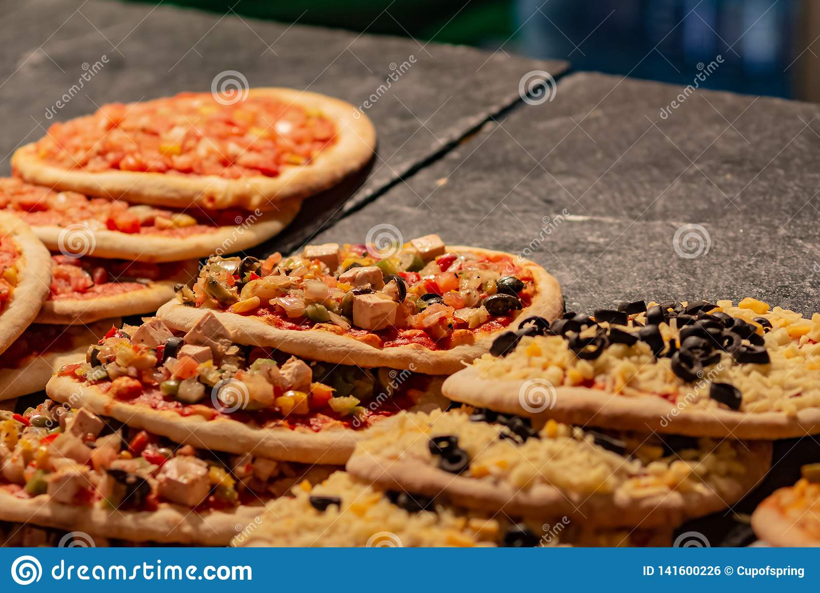 Много небольших горячих пицц на продаже на уличном рынке