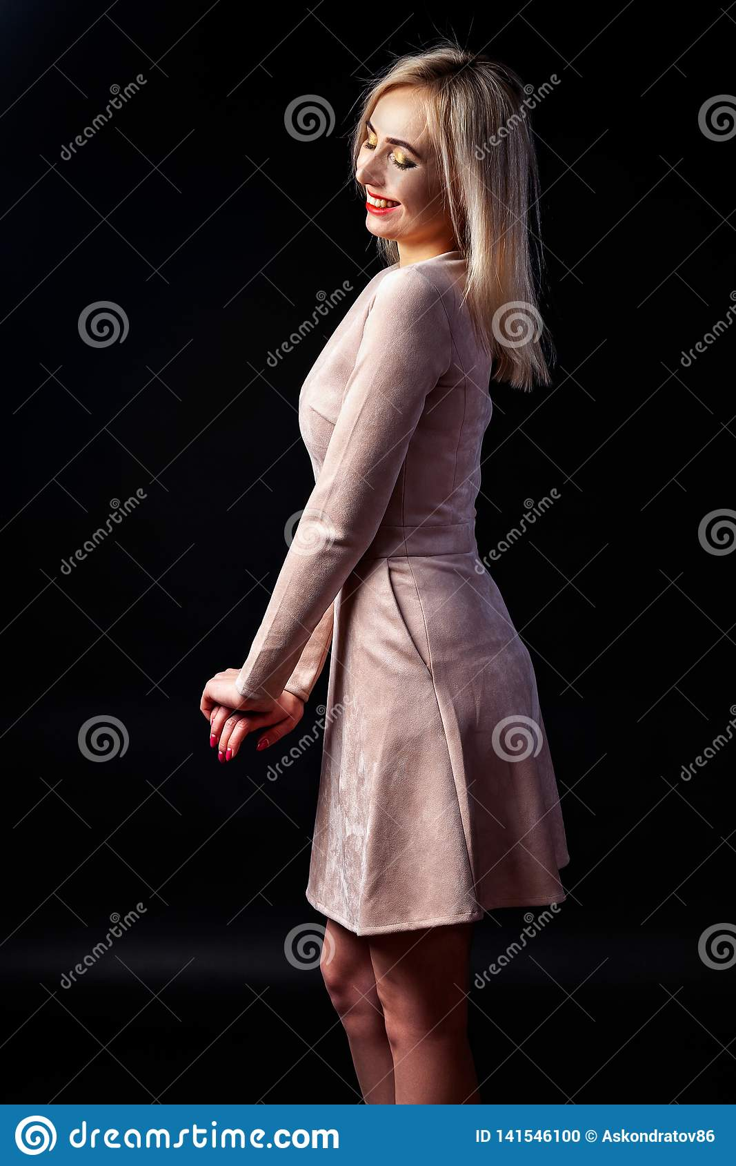 Молодая белокурая женщина с ярким макияжем и красными губами стоит в студии и усмехается на темной предпосылке в бежевом платье