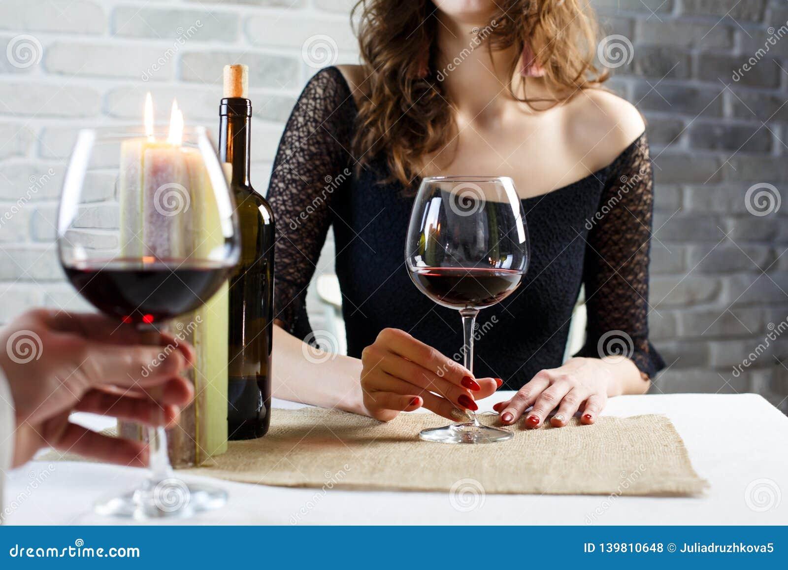 Молодая женщина выпивая красное вино на дате в ресторане
