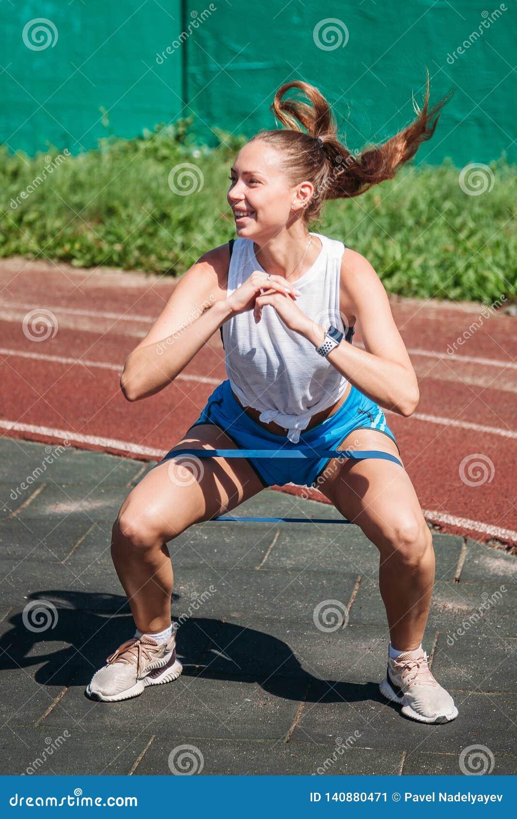 Молодая женщина выполняет тренировки высокого прыжка с эластичной резиновой лентой фитнеса на ее ногах на земле спорт