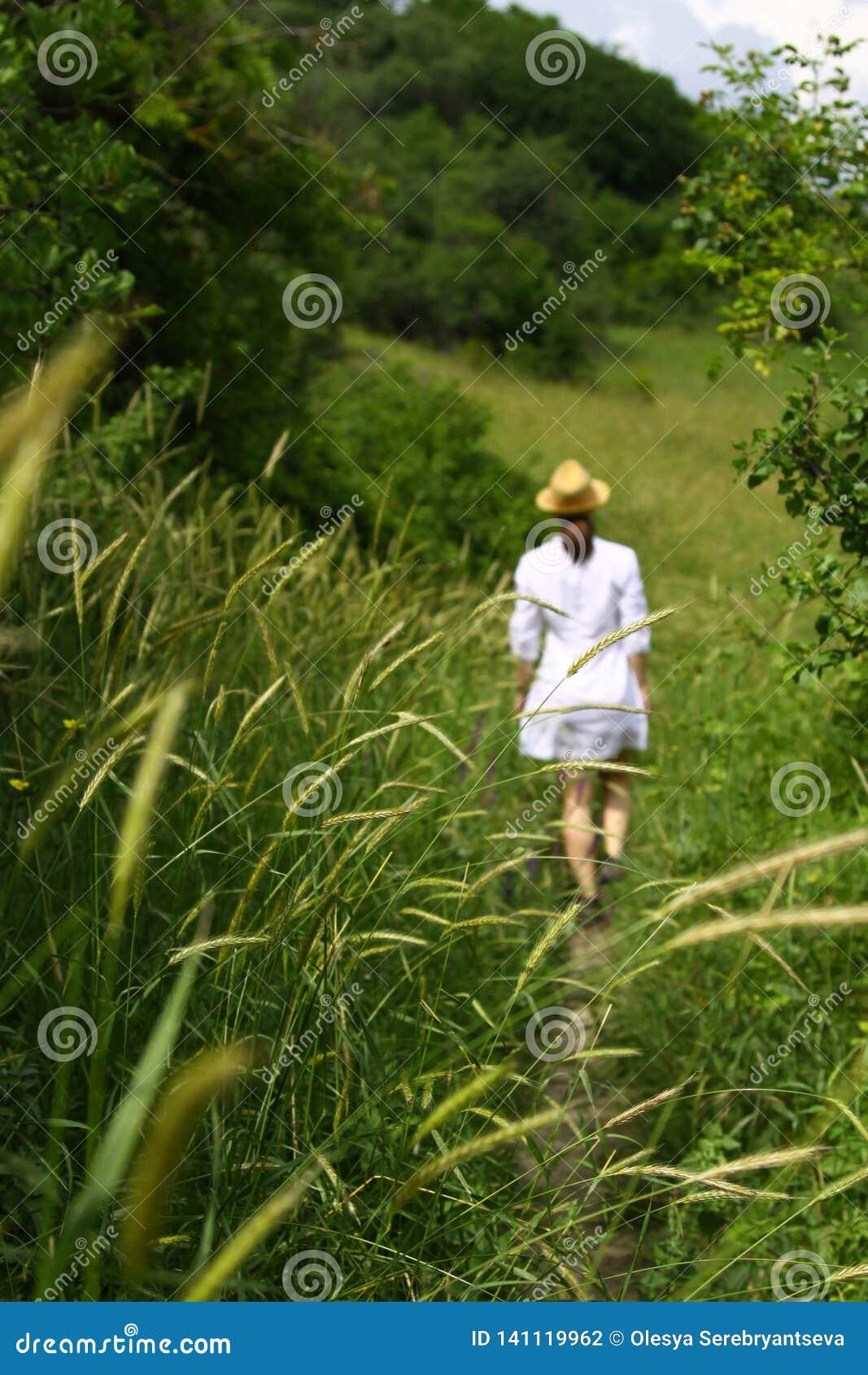 Молодая женщина в белых платье и шляпе идет вдоль пути среди зеленых трав