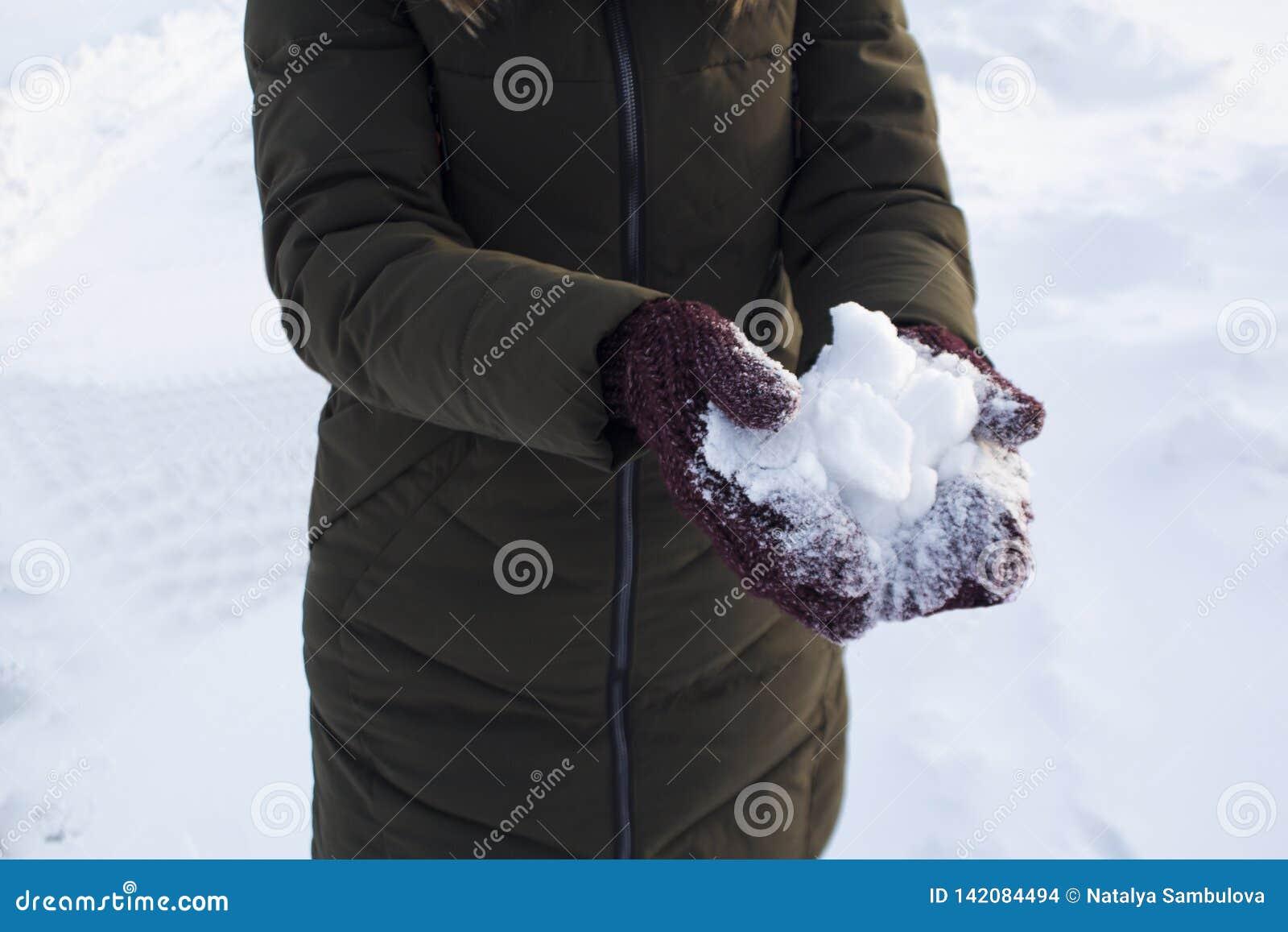 Молодая женщина держа снег в ее руках в mittens, зиму, потеху, утеху, спорт, воссоздание, детей