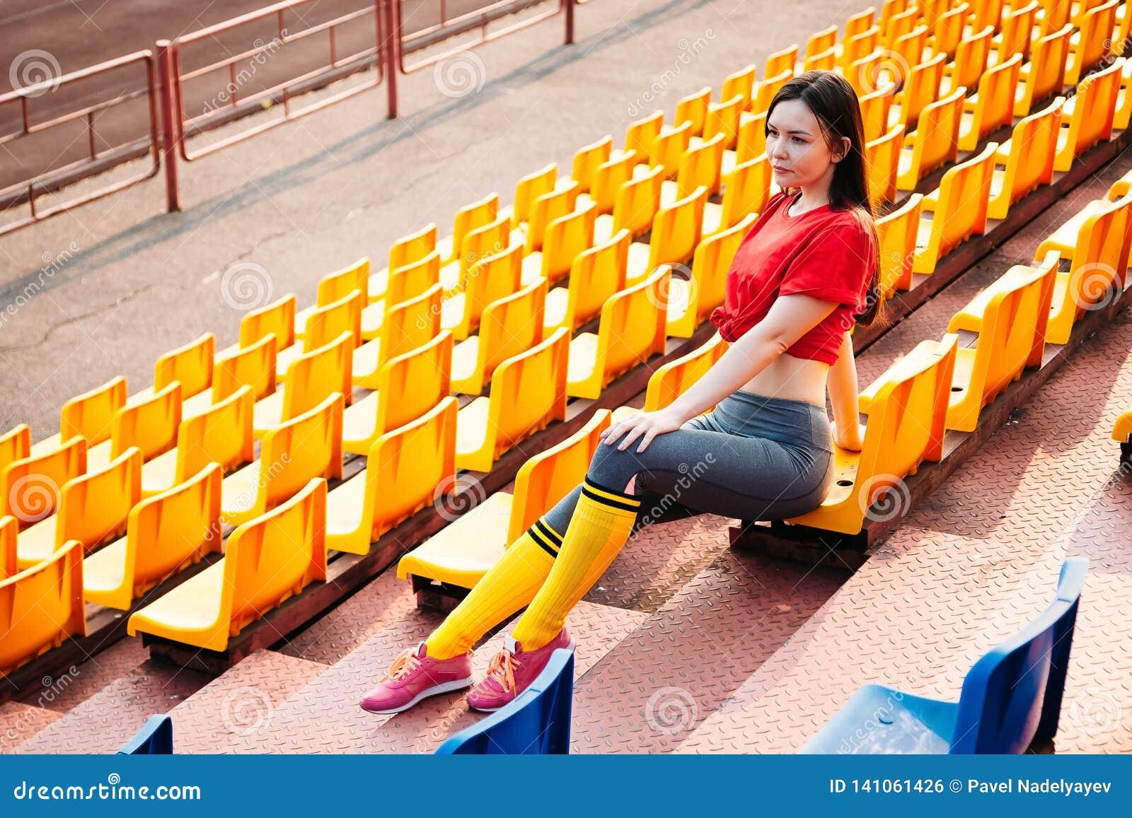 Молодая женщина спорт в sportswear на трибуне стадиона сидит на стенде