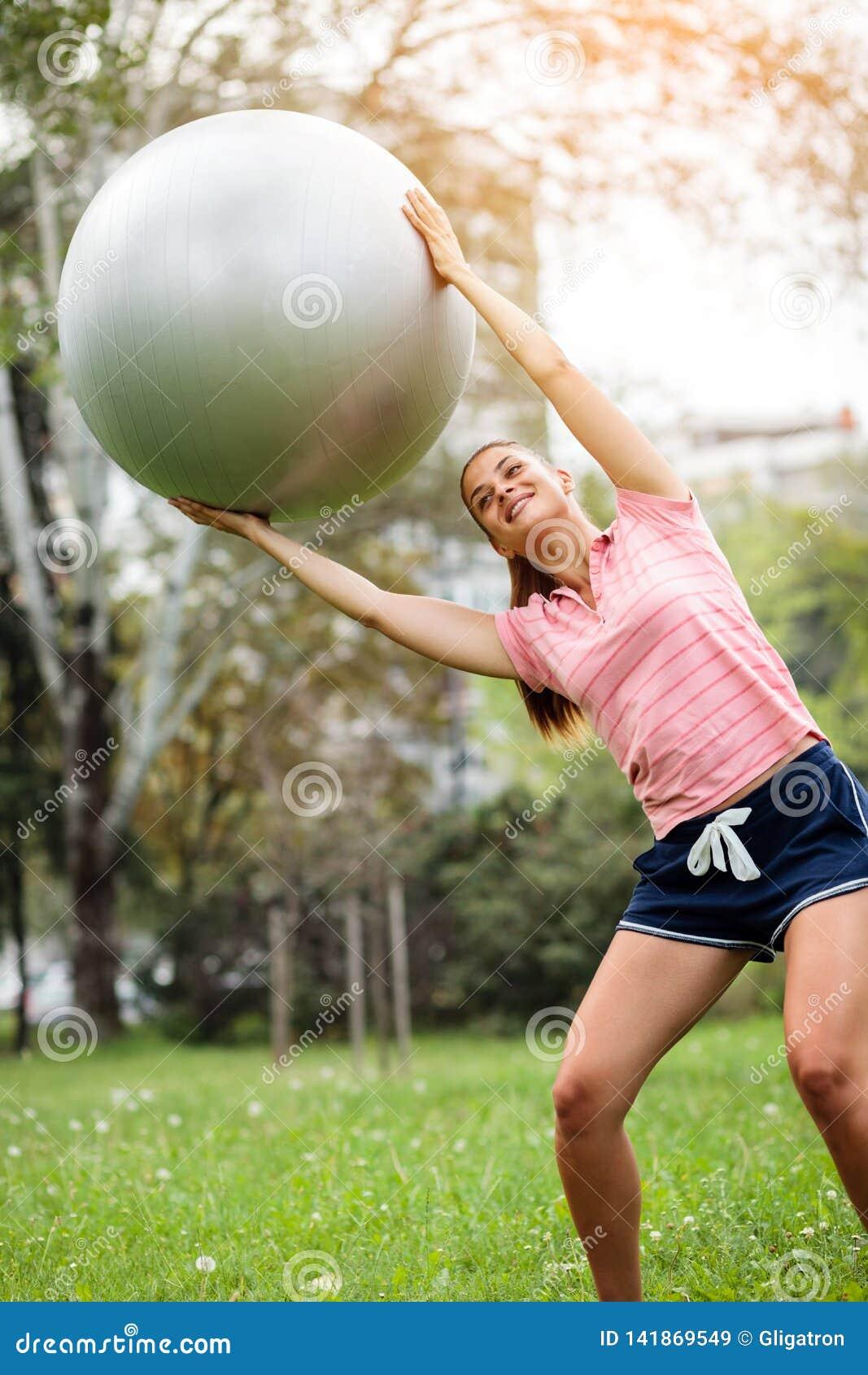 Молодая женщина работая с шариком pilates в парке Инструктор йоги держа шарик фитнеса над ее головой и тренировкой