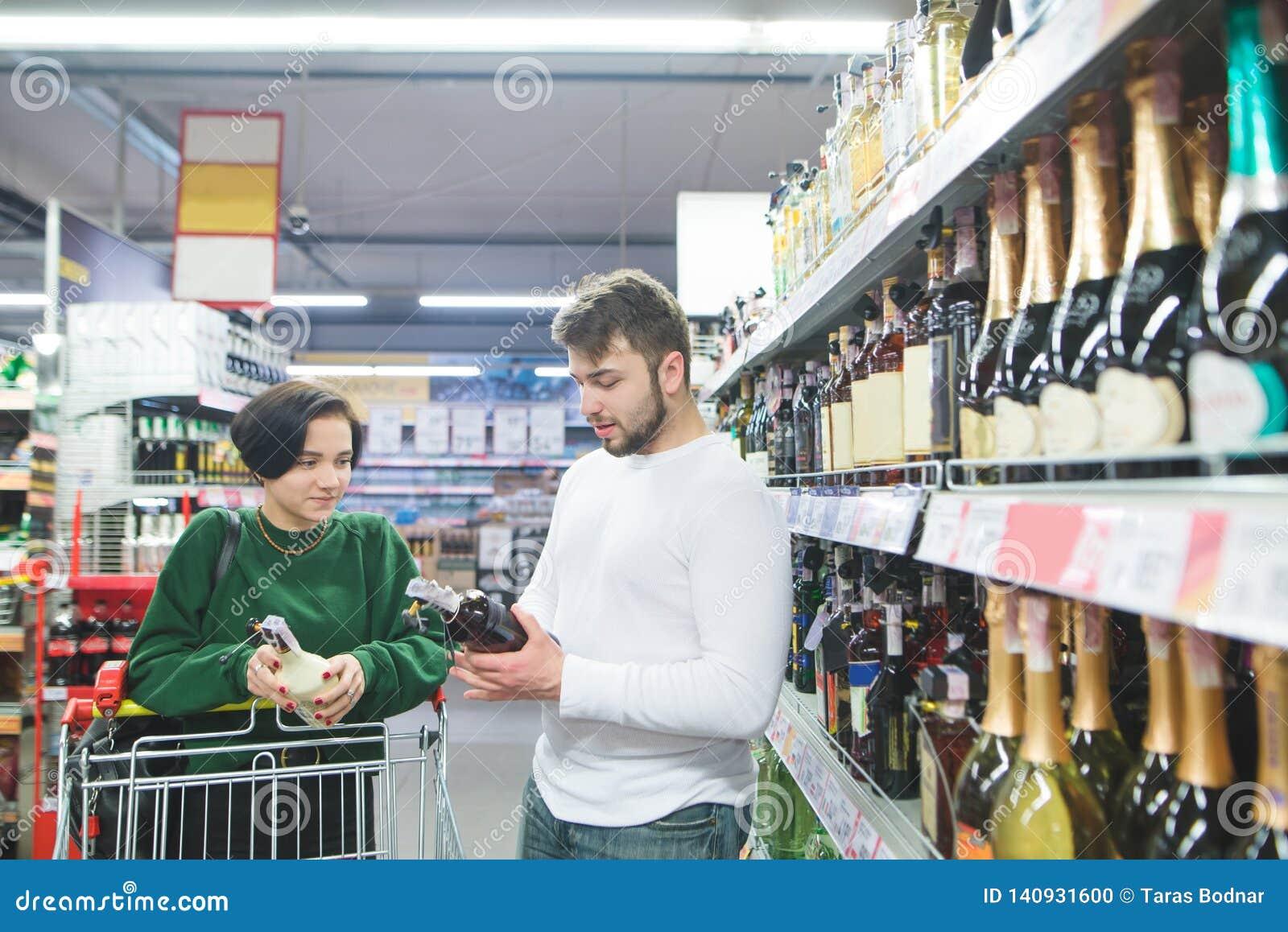 молодая красивая пара покупает алкоголь в магазине Пара выбирает вино на супермаркете