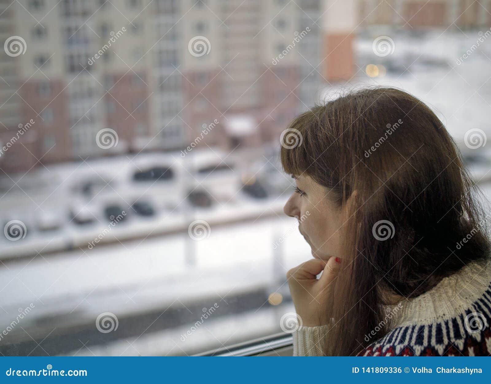Молодая милая женщина выглядящ грустная вне окном к улице снаружи, запачканная предпосылка
