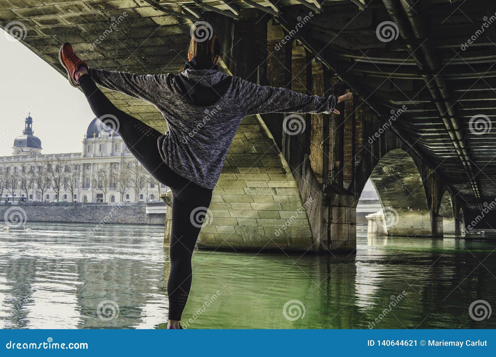 Молодая привлекательная женщина фитнеса делая тренировку и протягивая ноги в городе Великолепная архитектура на заднем плане