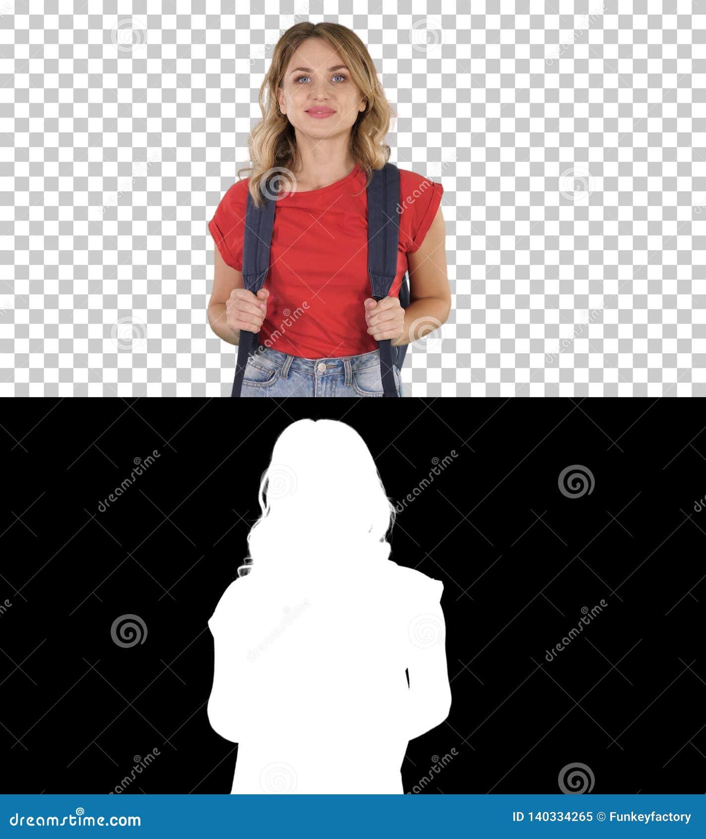 Молодая симпатичная женщина в случайной футболке с рюкзаком и джинсами идя, канал альфы