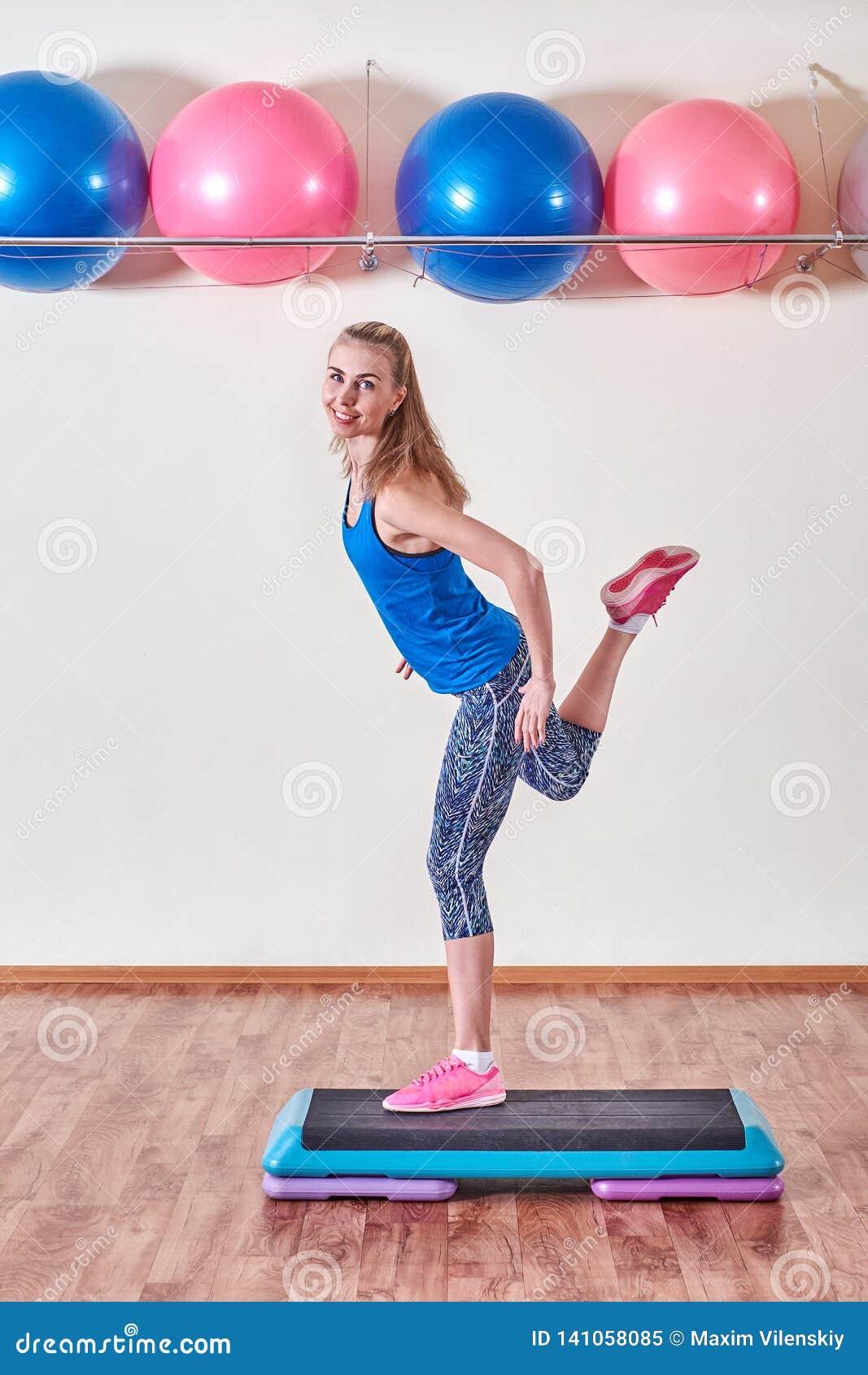 Молодая sportive женщина работая в спортзале используя платформу шага