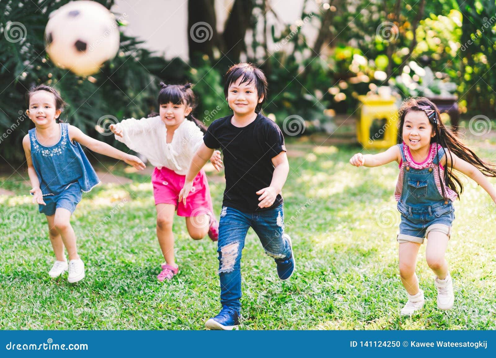 Молодые парни азиатской и смешанной гонки счастливые бежать играющ футбол совместно в саде Мульти-этническая группа детей, на отк
