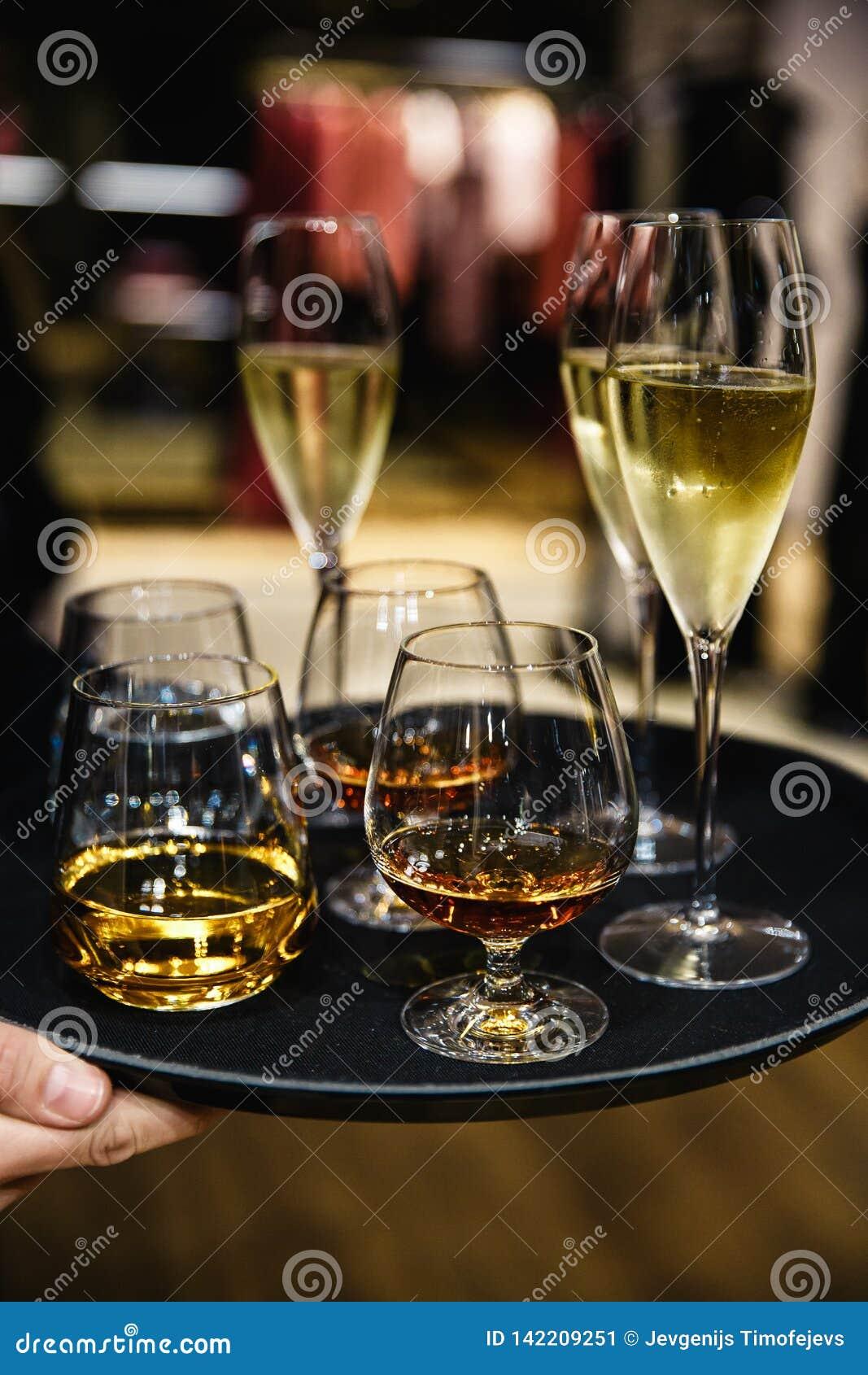 Молодое элегантное положение человека в ресторане, держа плиту со стеклами вина и коньяка, виски Стиль ` s человека