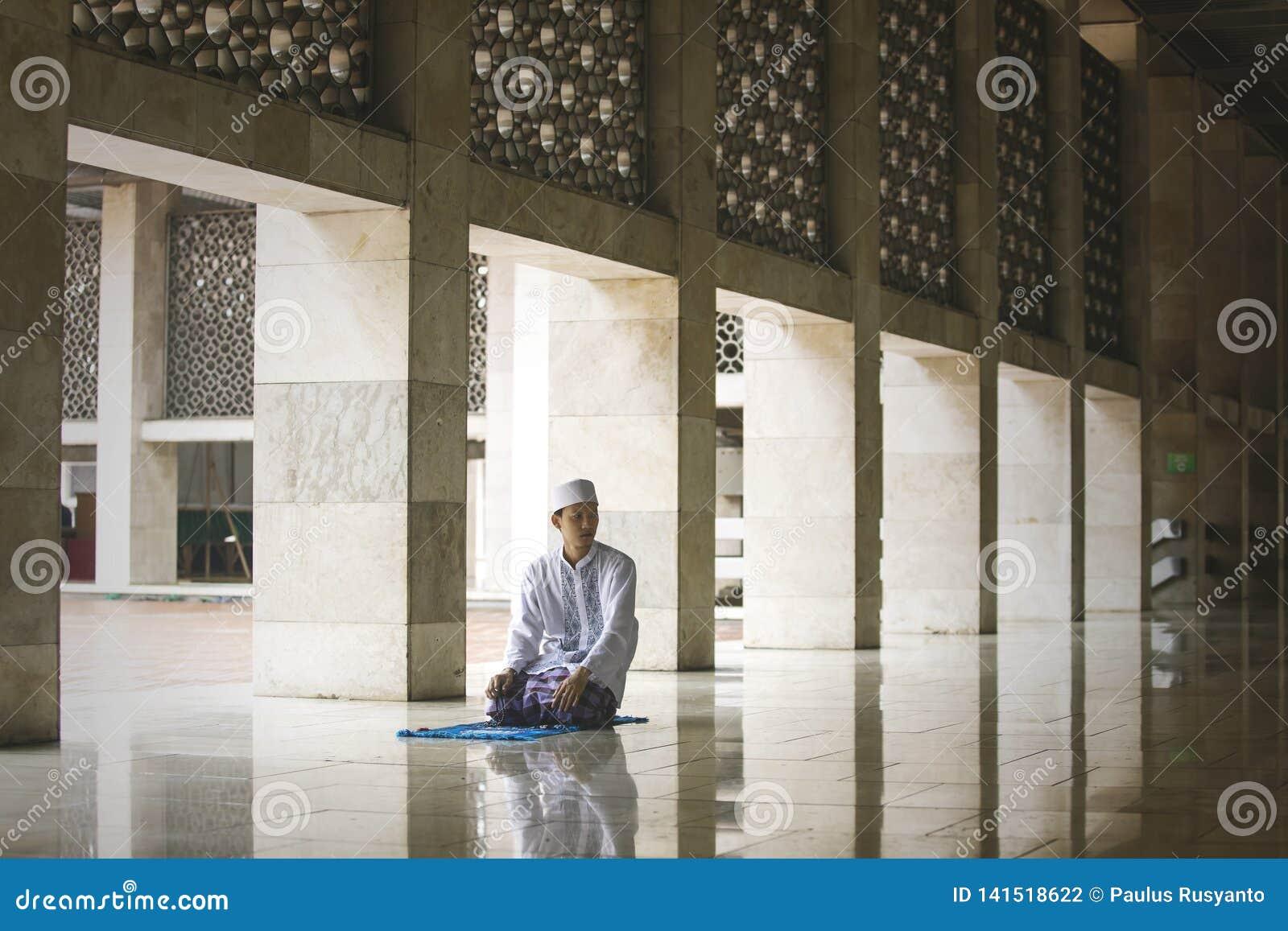 Молодой азиатский человек делая Salat на мечети