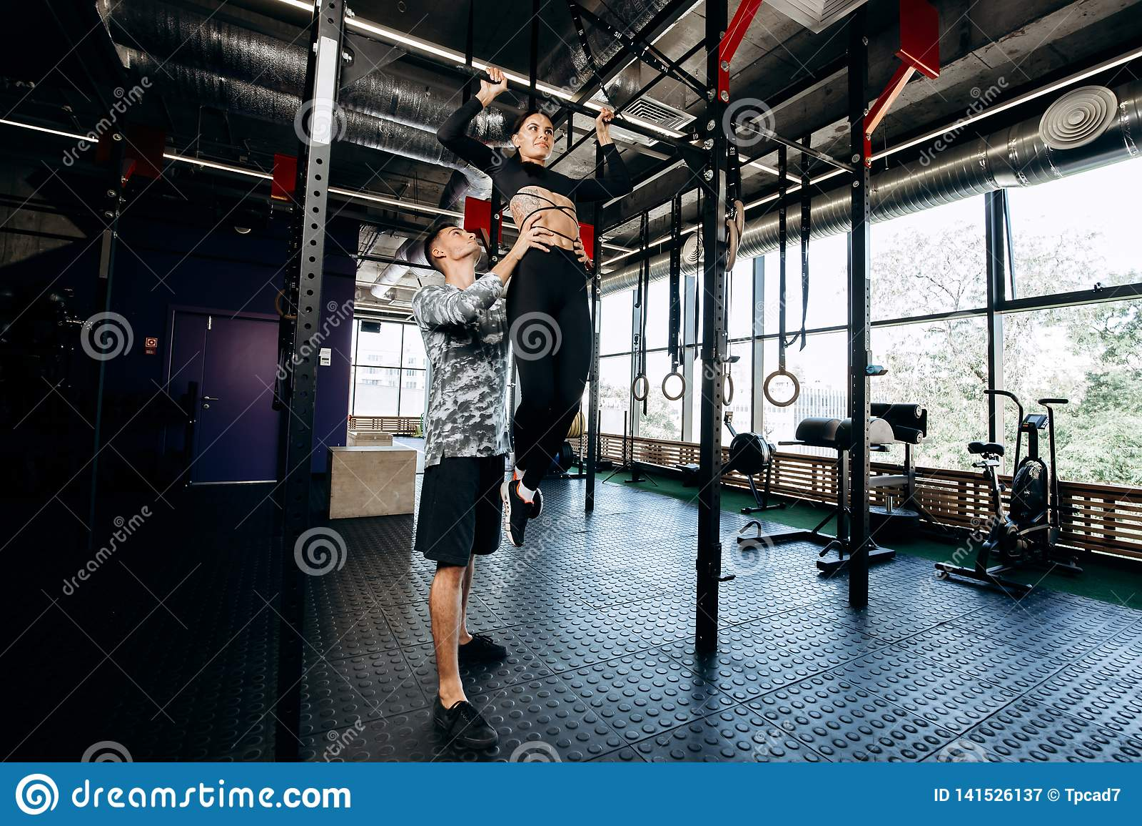 Молодой атлетический человек помогает худенькой милой девушке сделать тягу вверх на баре в спортзале