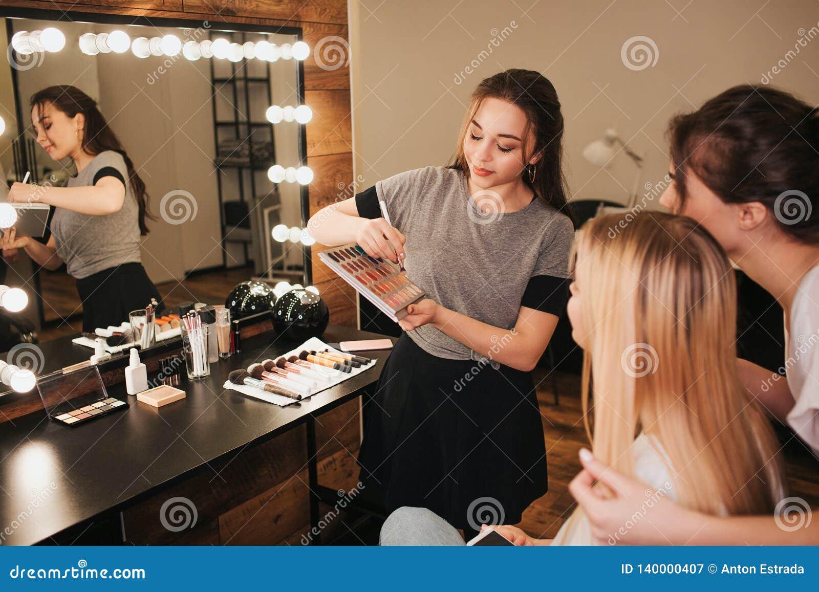 Молодой профессионал составляет художников с клиентом в комнате Женщина на левых палитре и щетке теней для век владением Блондинк
