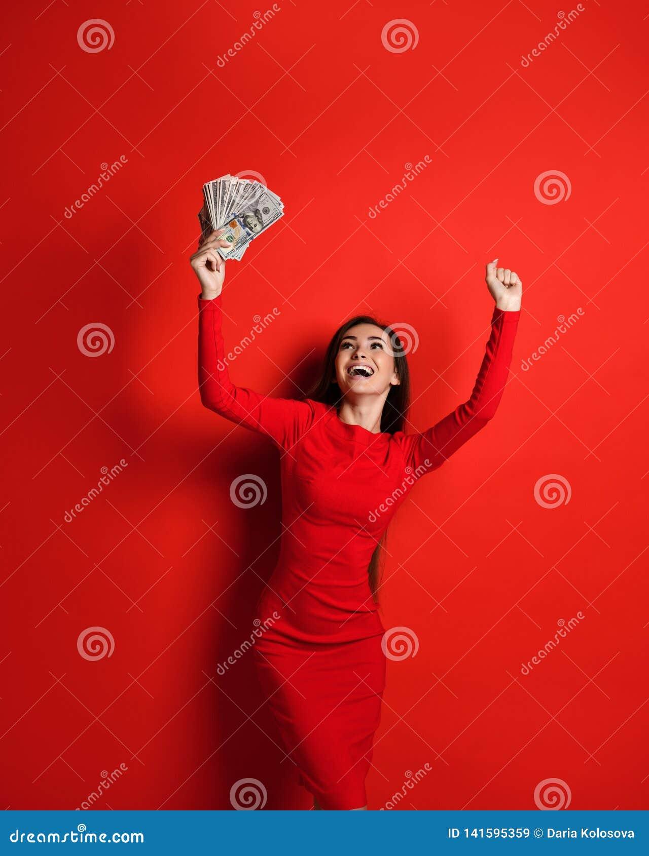 Молодой дерзкий брюнет в красном платье радуется в большое количество денег в ее руках она выигрывает