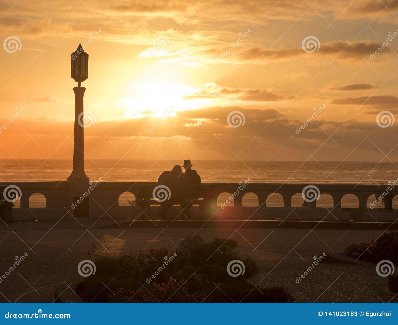 Молодой человек и женщина в любов сидя на стенде на seashore и наслаждаясь красивым заходом солнца