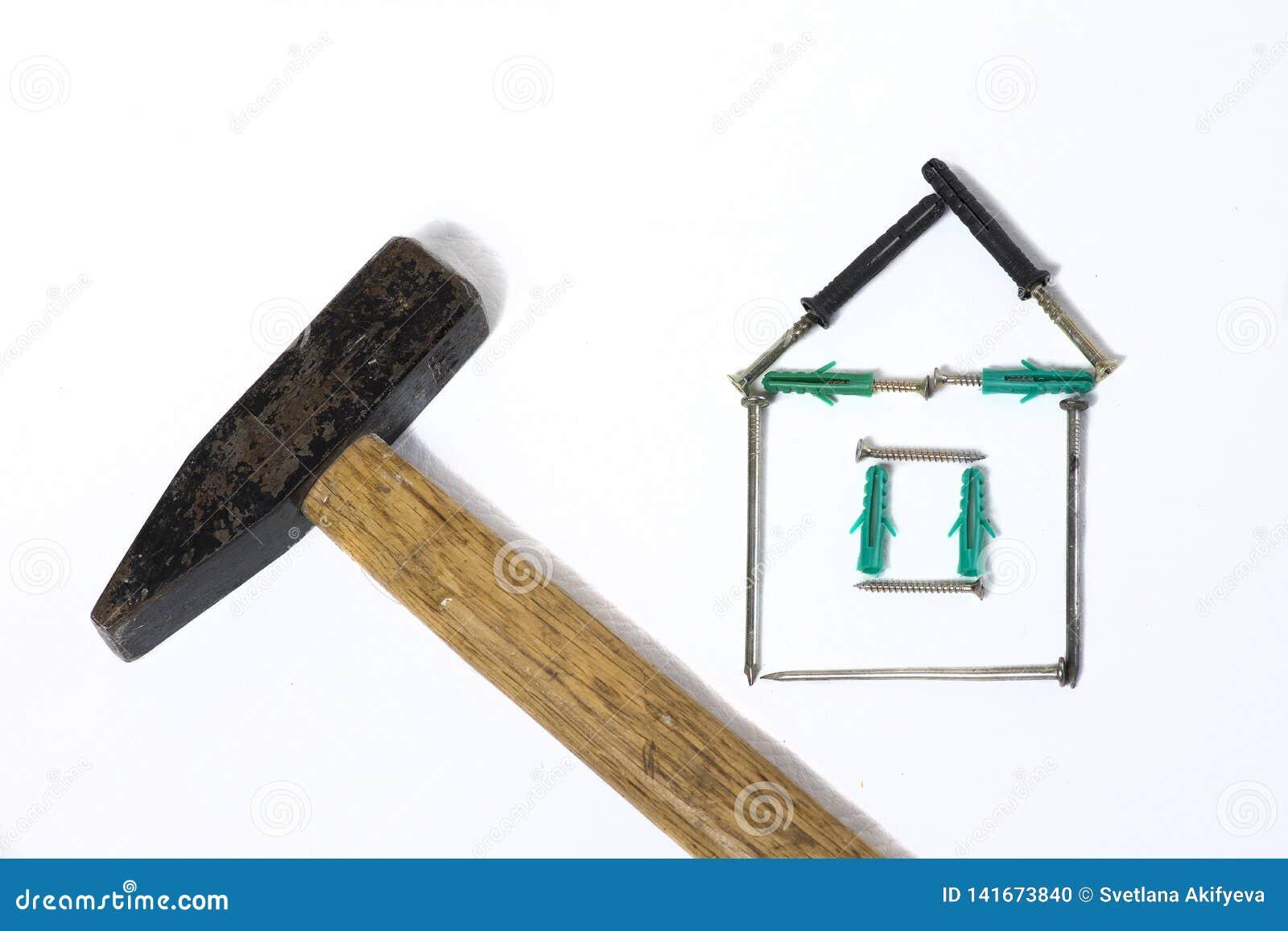 Молоток утюга с деревянным домом ногтя ручки на белой предпосылке