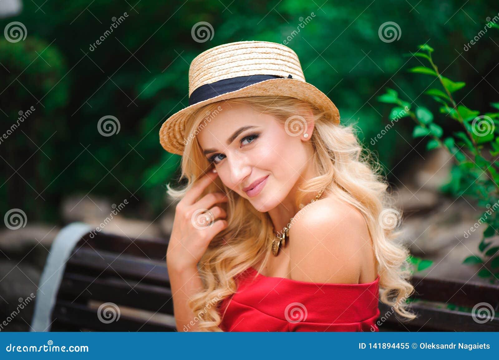 Модная привлекательная белокурая женщина в красном платье сидя на стуле