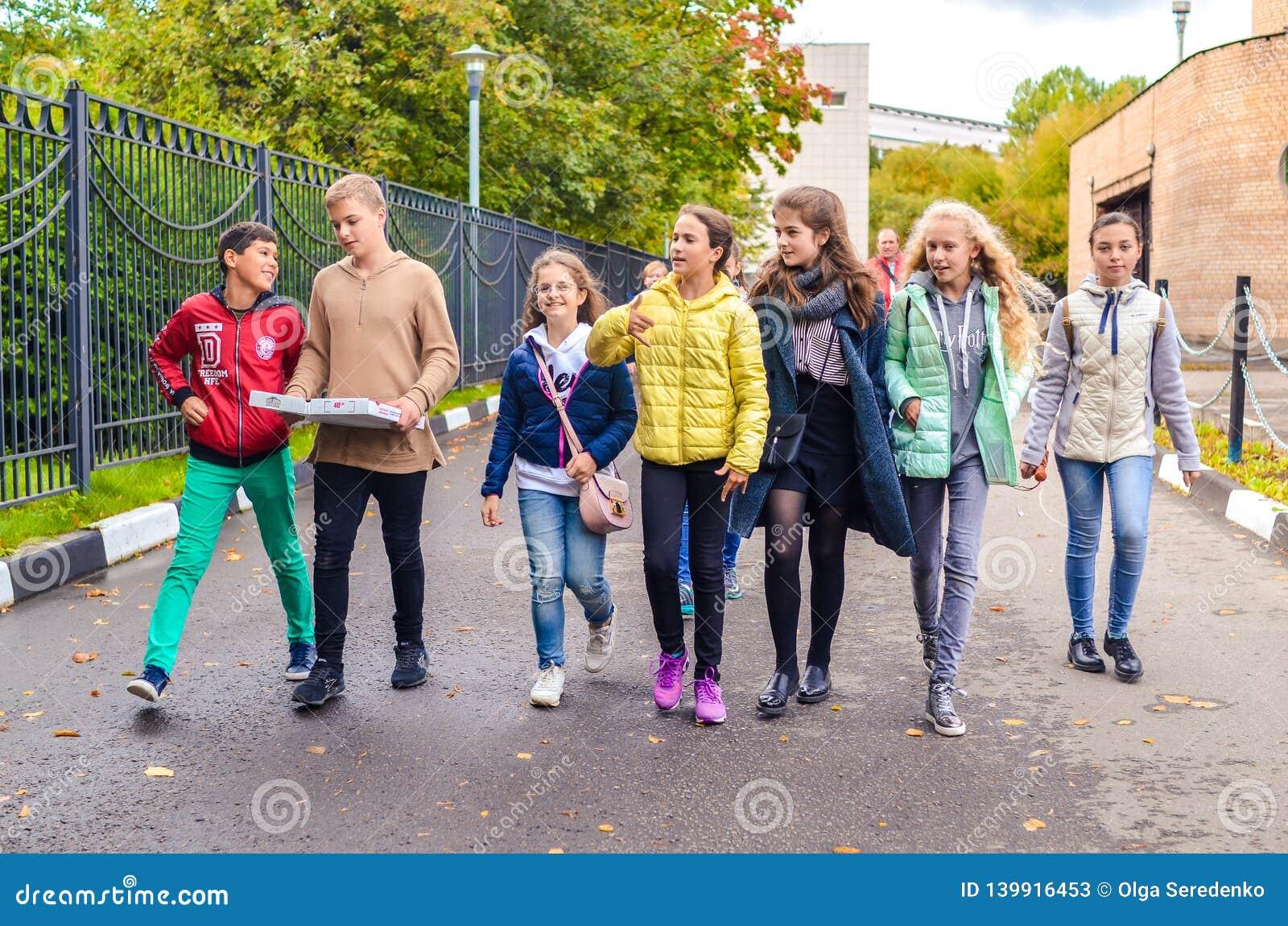 Москва, Россия, 23-ье сентября 2018 Группа в составе молодые мальчики и девушки говоря и идя вниз с дороги