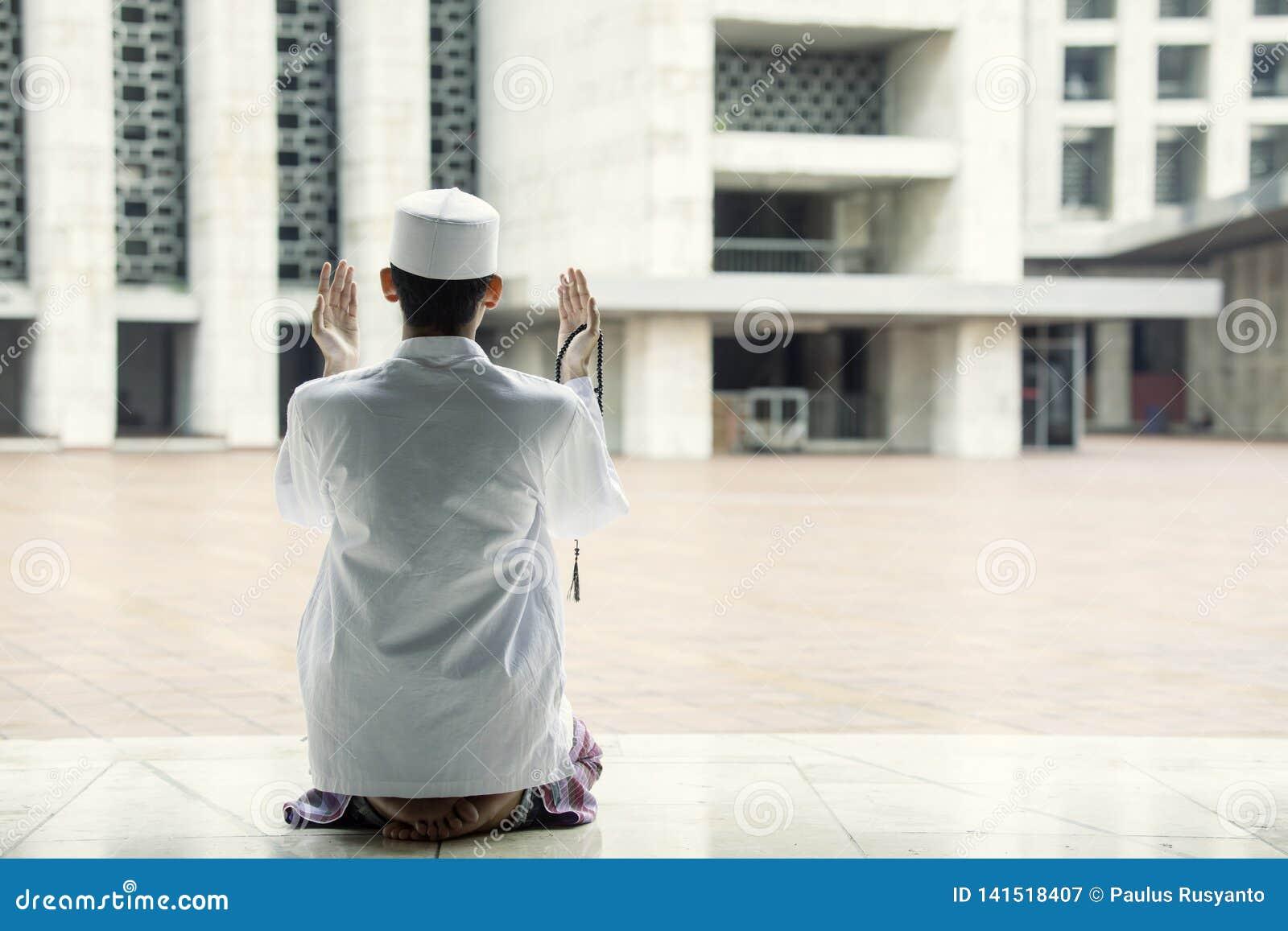 Набожный человек молит к Аллаху в мечети