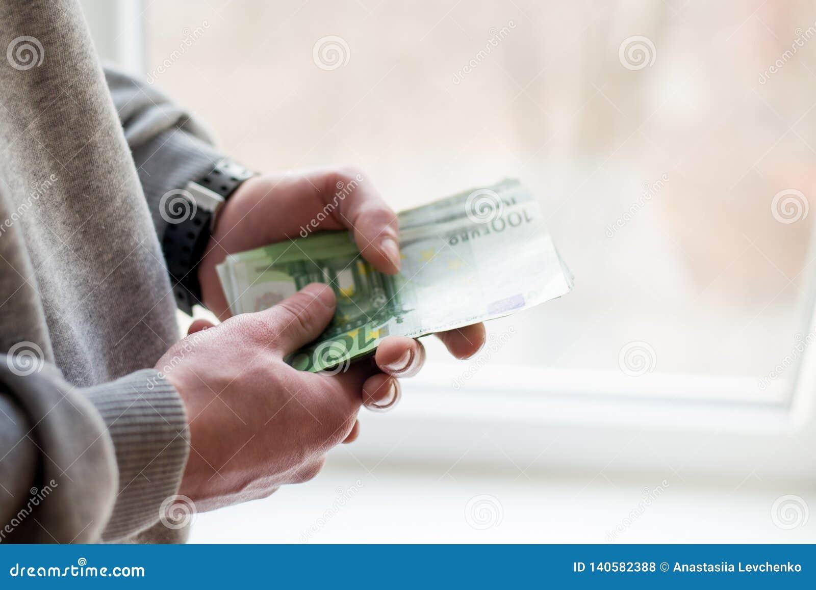 накрените веревочка примечания дег фокуса 100 евро 5 евро бумажные банкноты евро в руке человека человек дает взятку