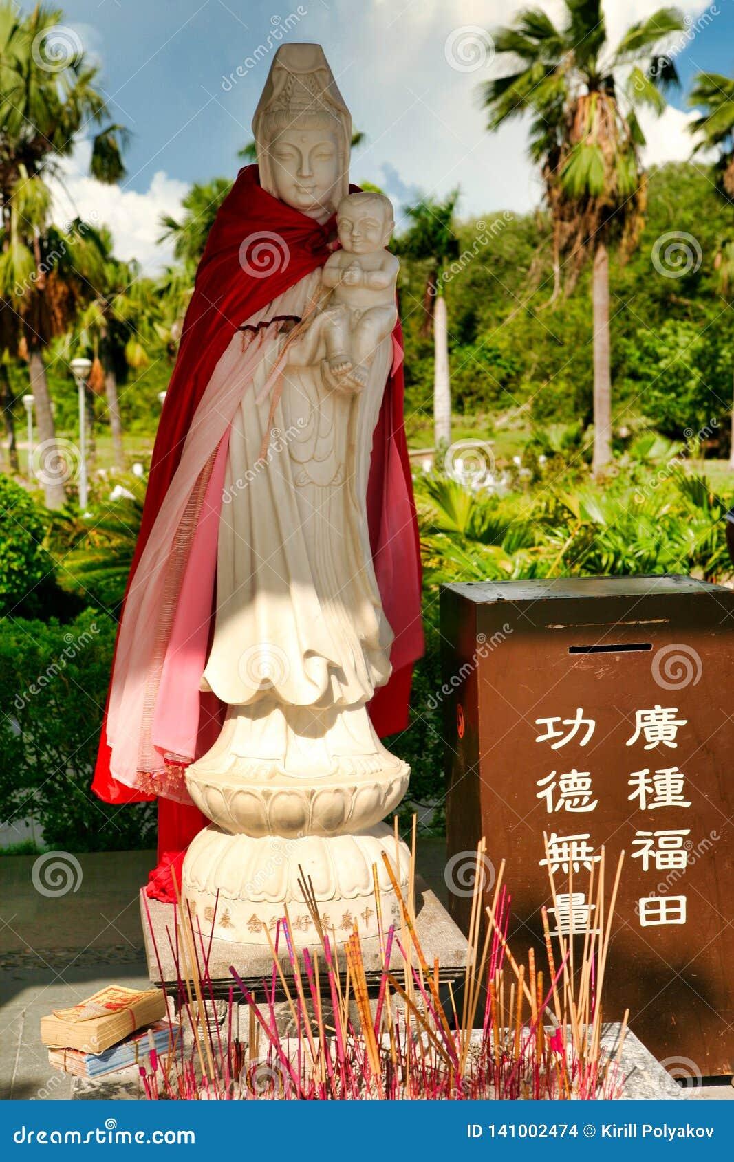 """Небольшая статуя богини Guanyin с младенцем в ее оружиях в парке Nanshan Маленькая коробка говорит: """"для пожертвований """"Хайнань"""