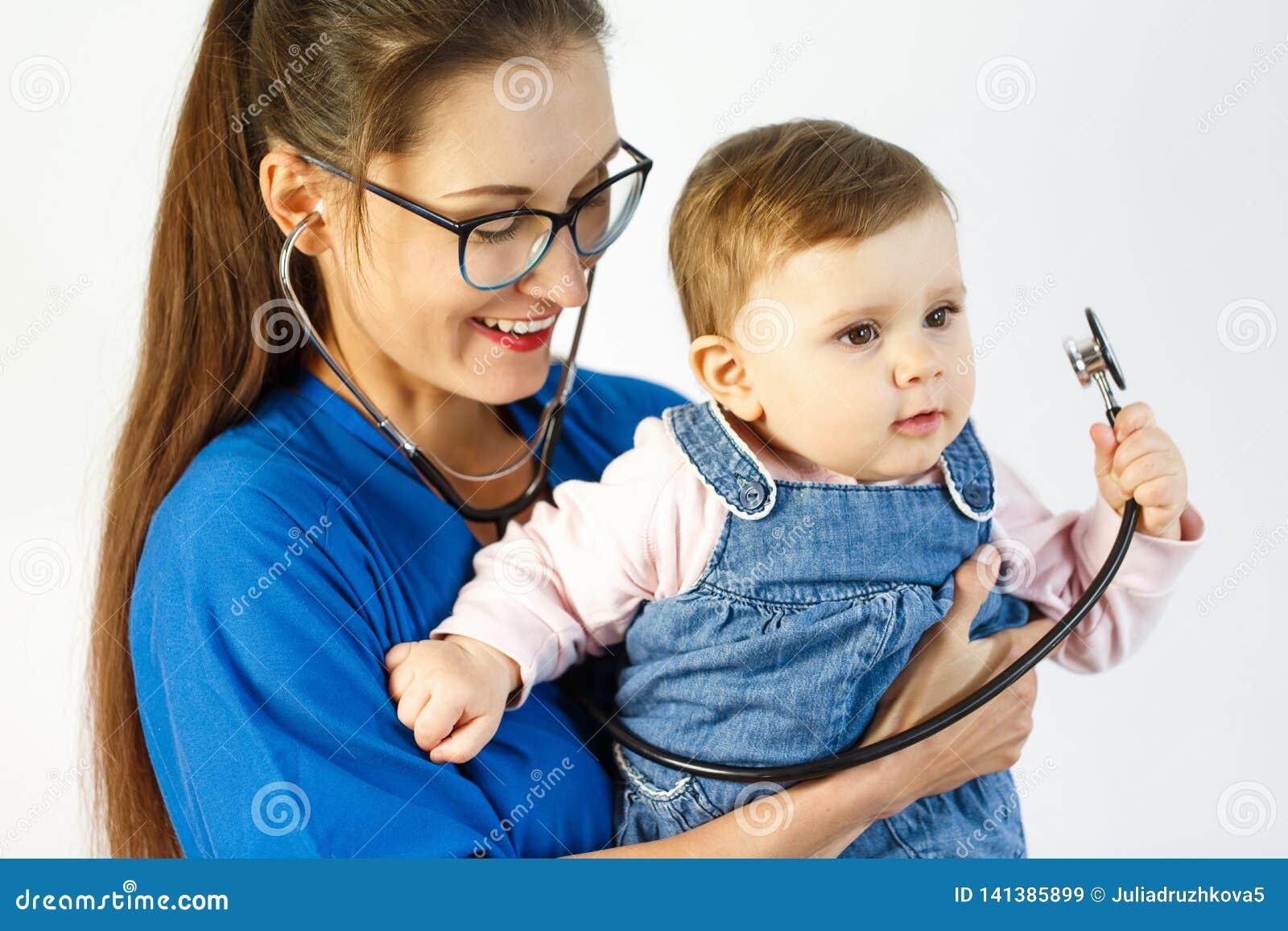 Небольшой ребенок в руках доктора держа стетоскоп