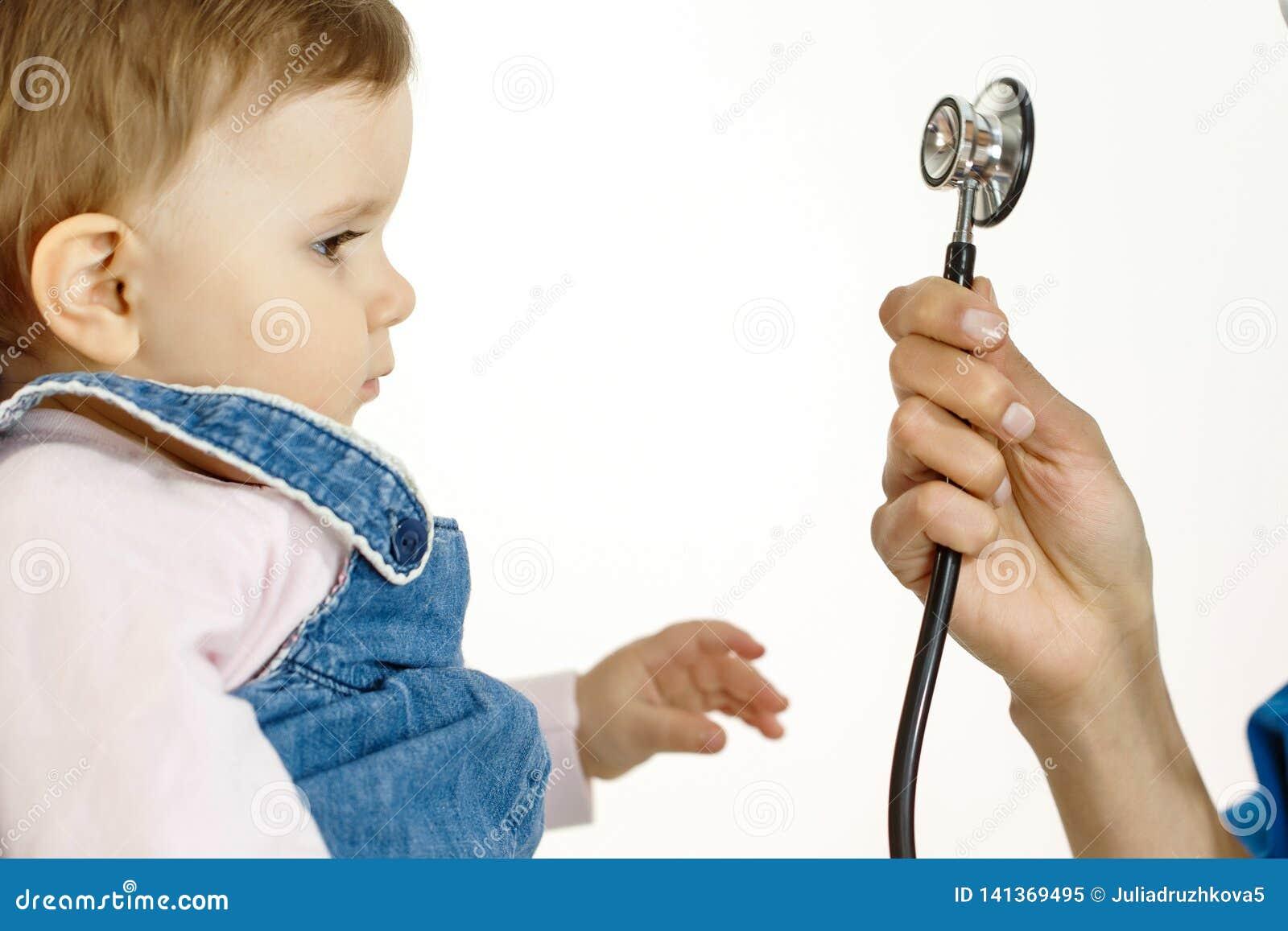 Небольшой ребенок смотрит стетоскоп и вытягивает его руку к нему