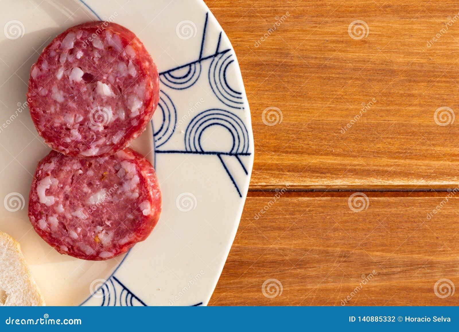 Некоторые куски салями на старой керамической плите на деревянной деревенской таблице Еда для закуски