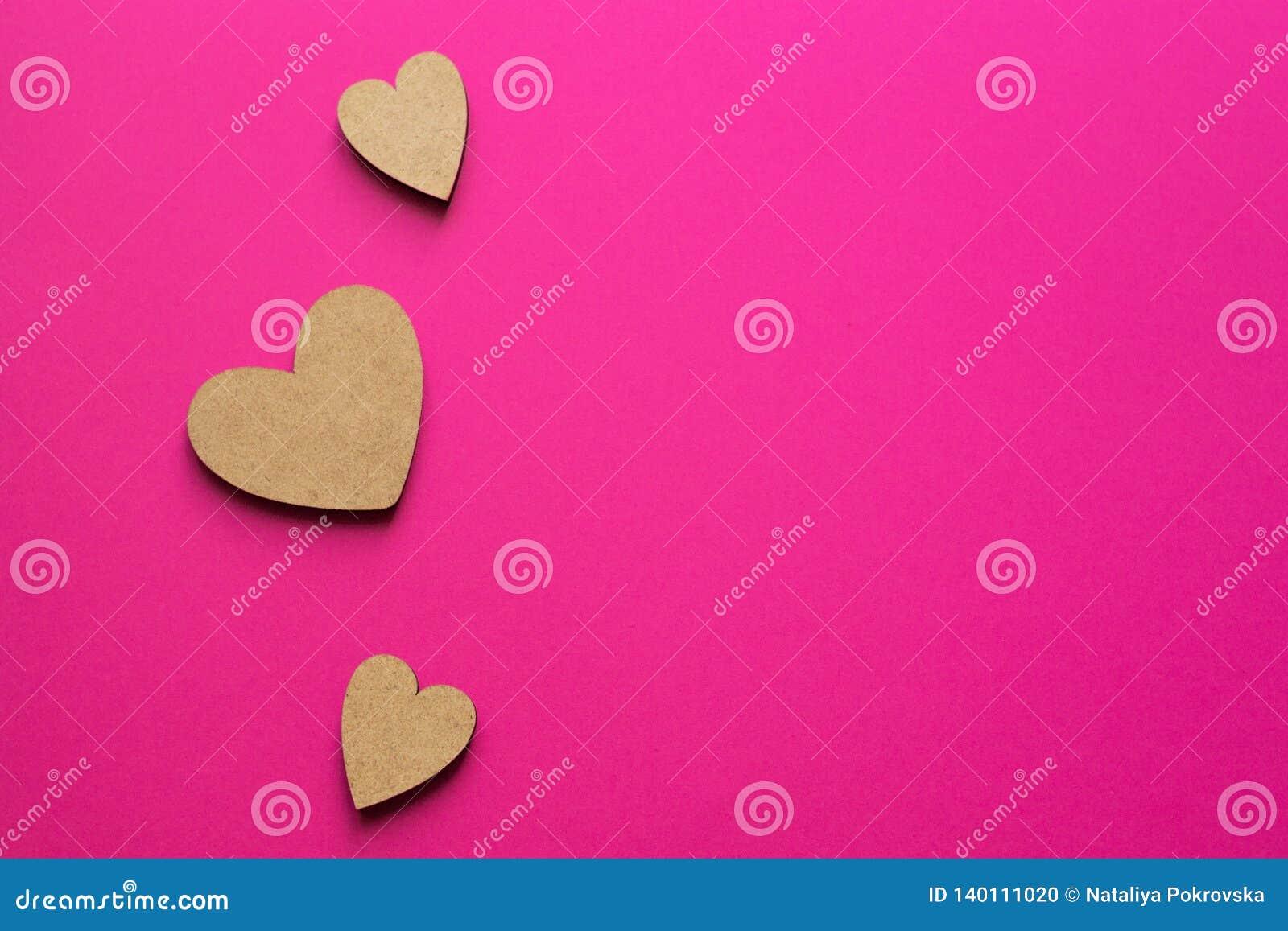Немногое деревянные сердца на розовой предпосылке Романтичный состав с космосом экземпляра для приветствовать