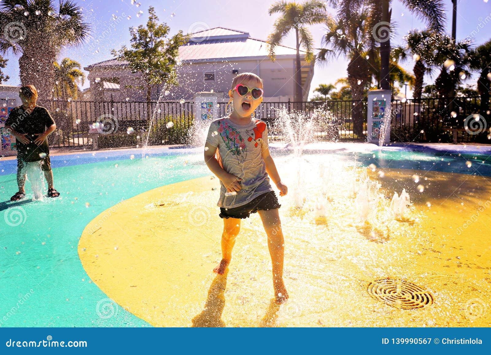 Немногое ребенок играя в воде на парке выплеска на летний день