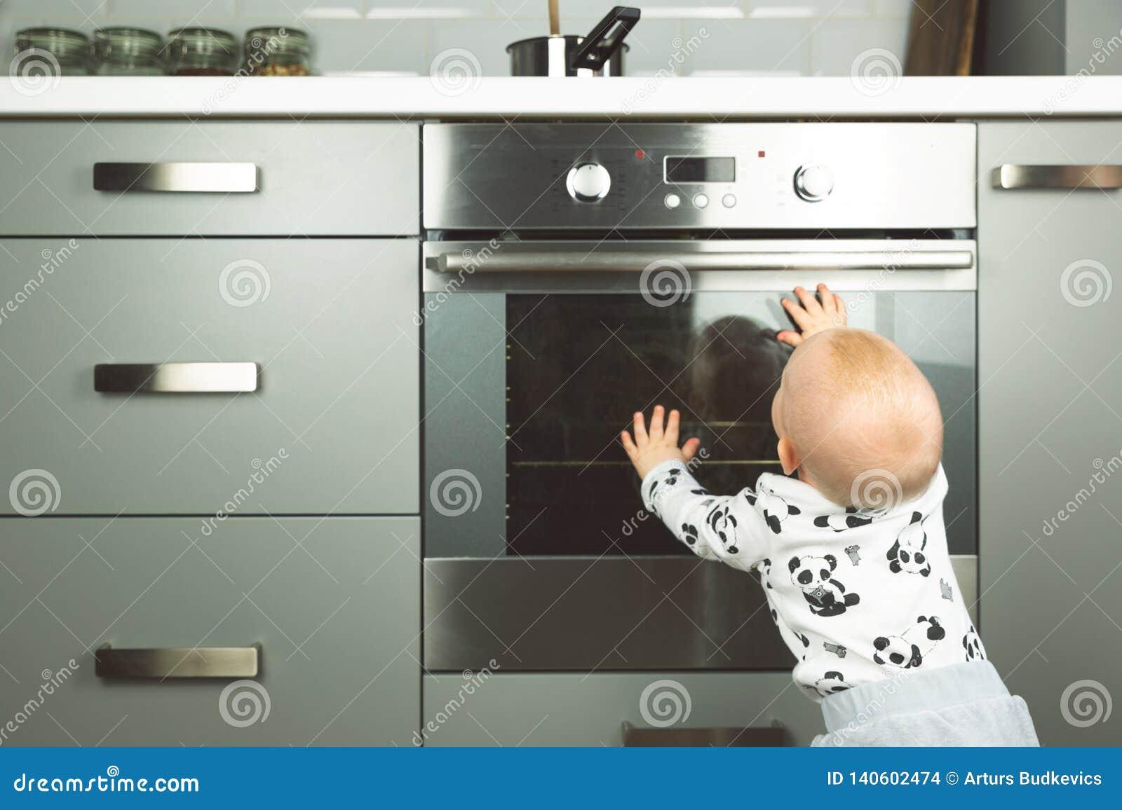 Немногое ребенок играя с электрической плитой в кухне Безопасность младенца в кухне