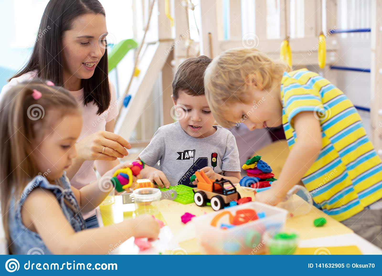Няня младенца играя с детьми в детском саде