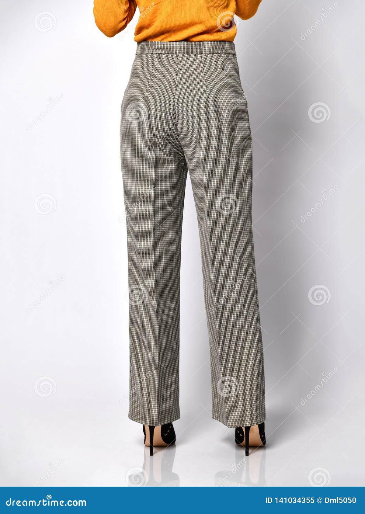 Ноги молодой женщины идя в новые серые классические брюки в коробке от костюма на белом