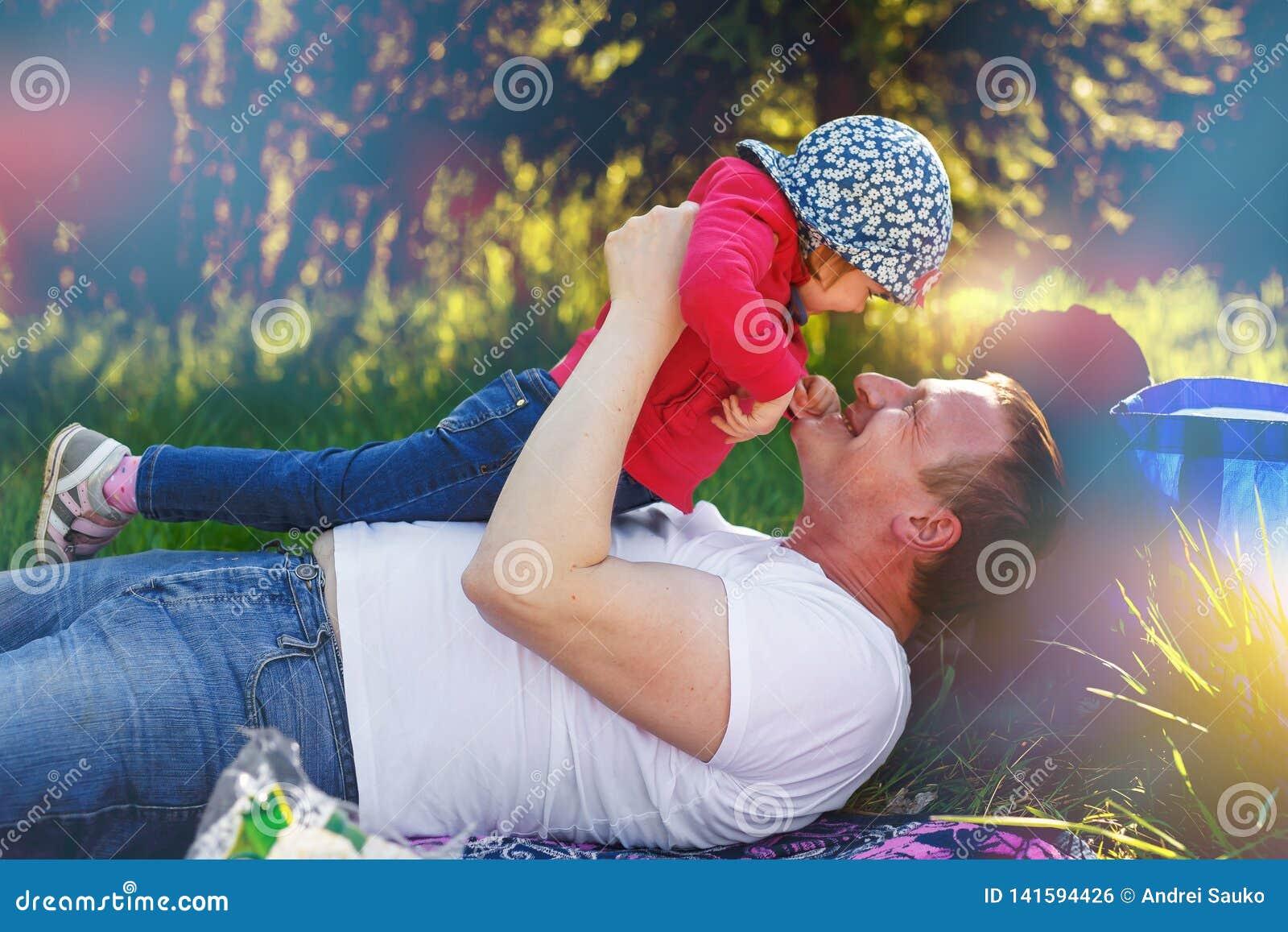 Папа играет с его дочерью в парке