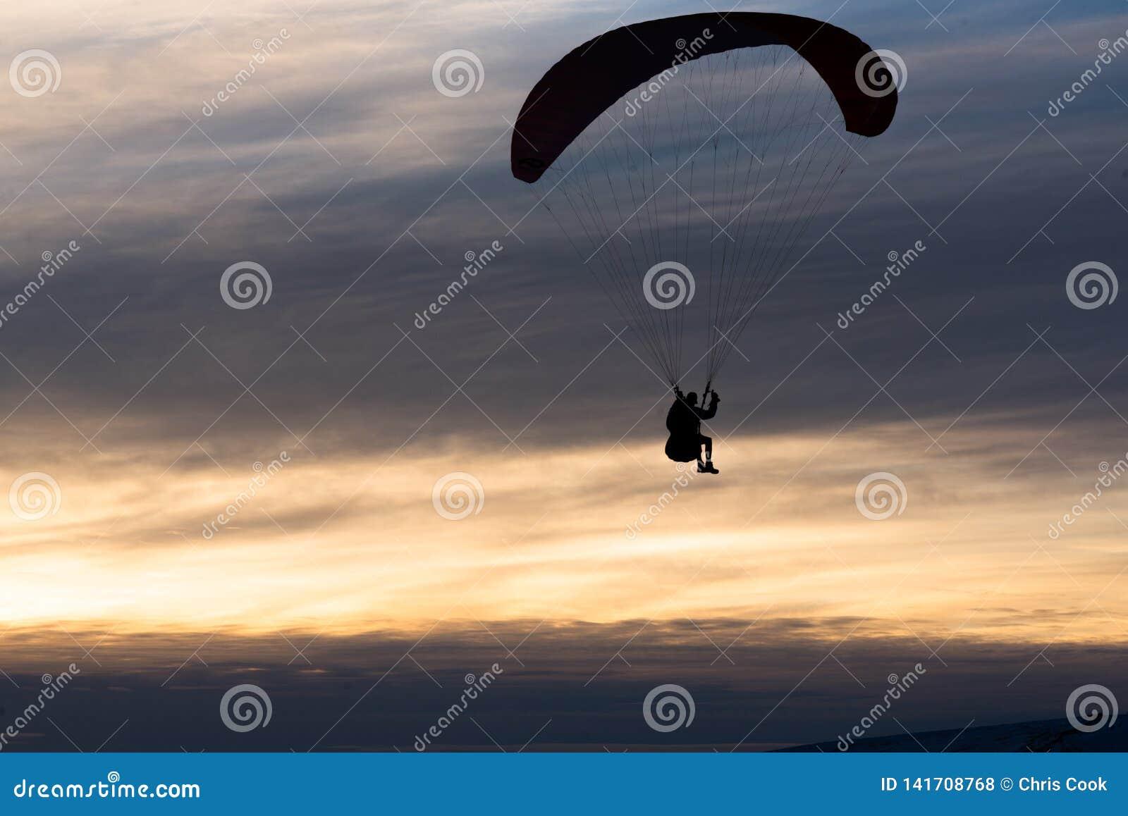 Парапланеризм человека вниз с горы против пасмурного захода солнца в зиме