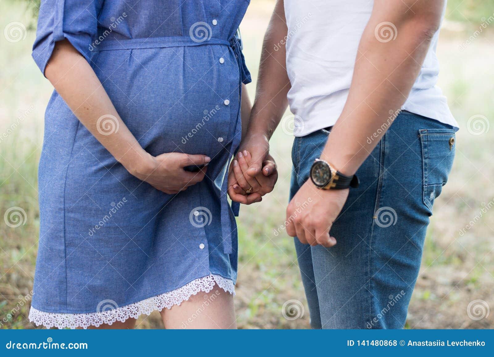 Пары в прижиматься любов беременный, ждать младенец идя в парк в теплом солнечном дне Беременность голубая девушка платья