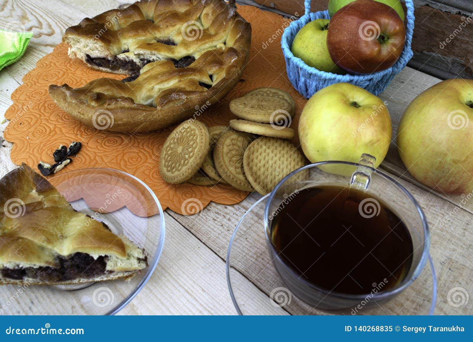 Пирог, кусок яблочного пирога с вишней и грецкими орехами, чашка чаю, яблоки в корзине, грецкие орехи и печенья на таблице