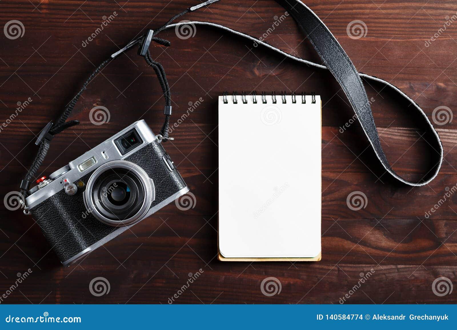 Пустая страница блокнота и современная камера в классическом стиле на темном коричневом деревянном столе
