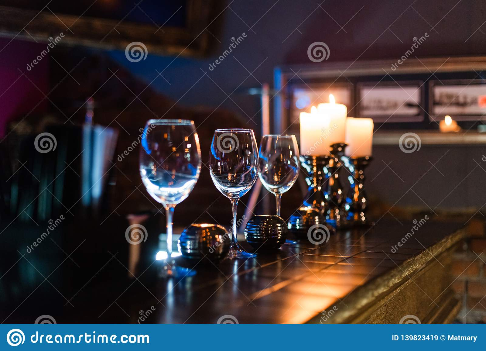 Пустые бокалы и свечи с предпосылкой светов освещения