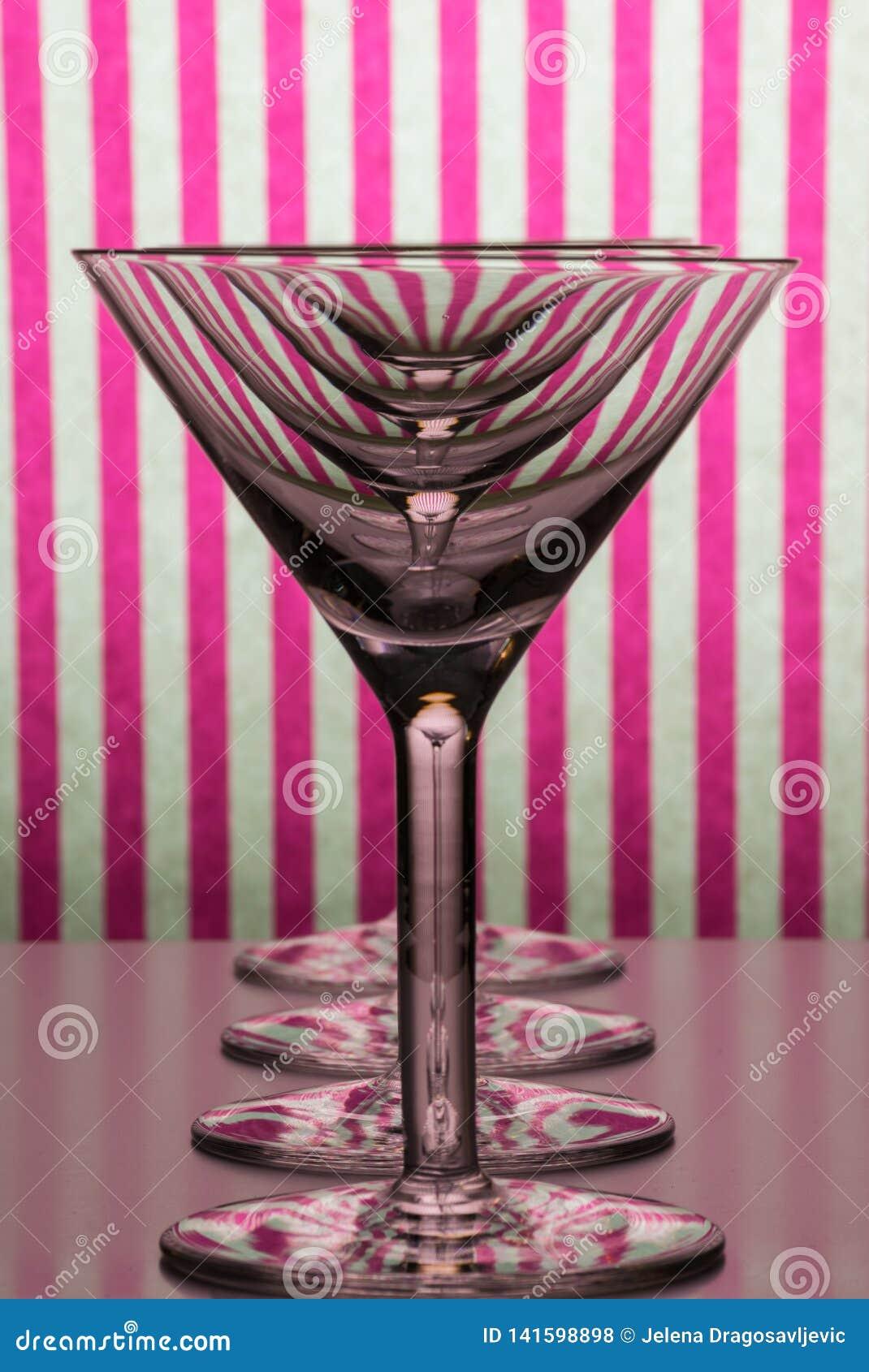 4 пустых стекла для Мартини и положение вермута в линии с белой и розовой striped предпосылкой