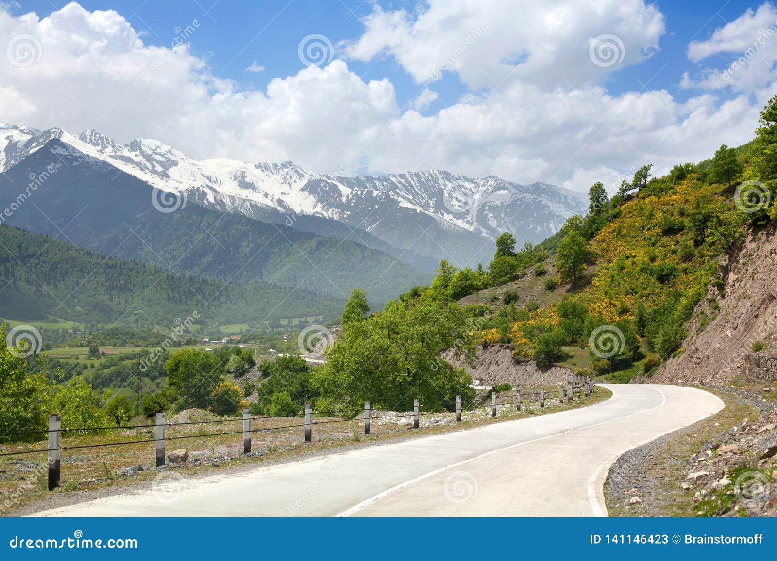 Пустой серпентин дороги в горах, голубых облаках skywith, горных пиках в снеге и предпосылке зеленых холмов