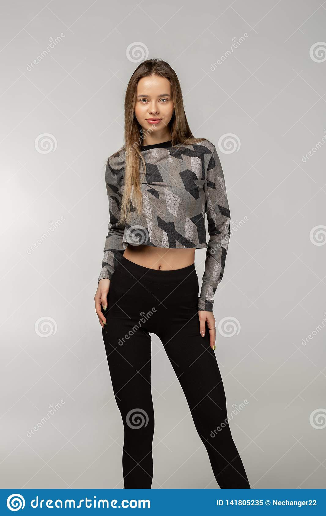 Привлекательный милый женский инструктор фитнеса одетый в черном sportwear