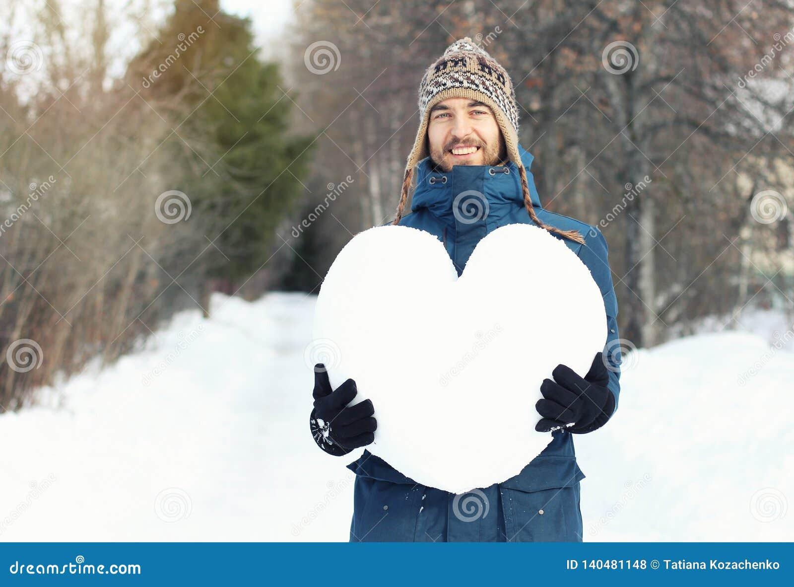 Привлекательный усмехаясь человек держа огромное сердце сделанный снега в падении леса зимы в любовь Объявления любов, романтичны