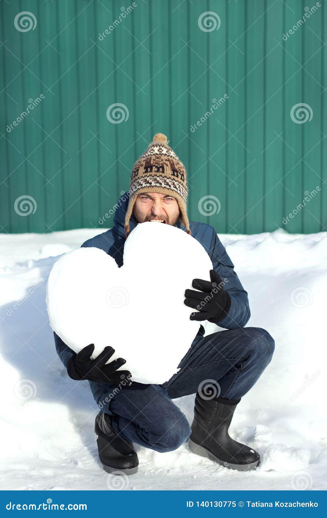 Привлекательный человек хипстера в одеждах зимы сдерживает огромное сердце сделанное снега На зеленых стене и предпосылке смещени
