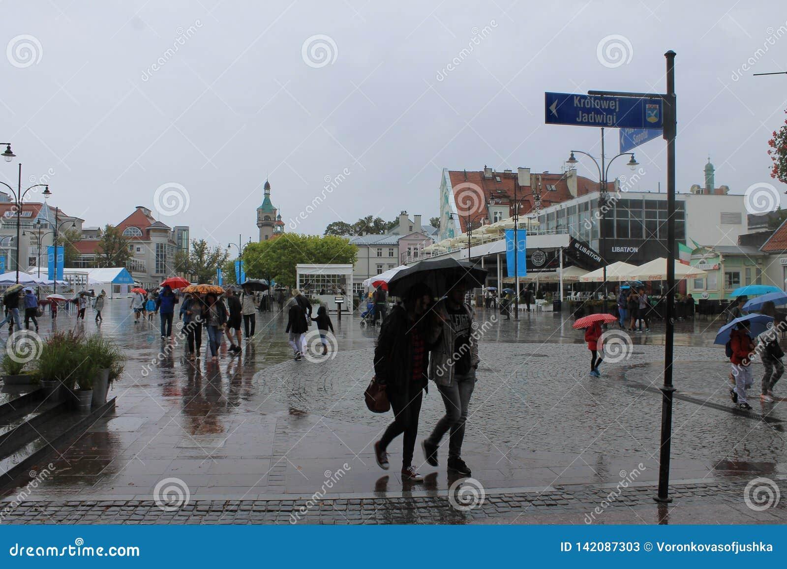 Прогулка в Sopot Польше с людьми идя под зонтики в дожде
