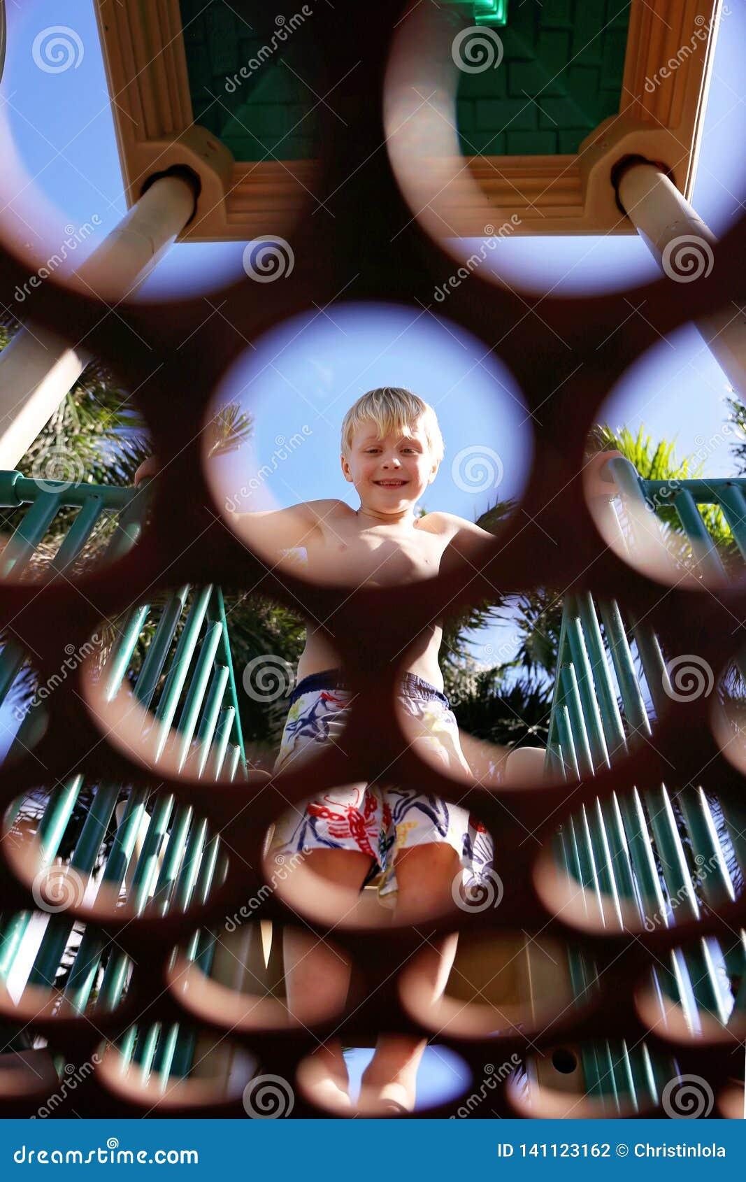 Промежуток времени маленького ребенка усмехаясь смотря через круги в платформе на спортивной площадке