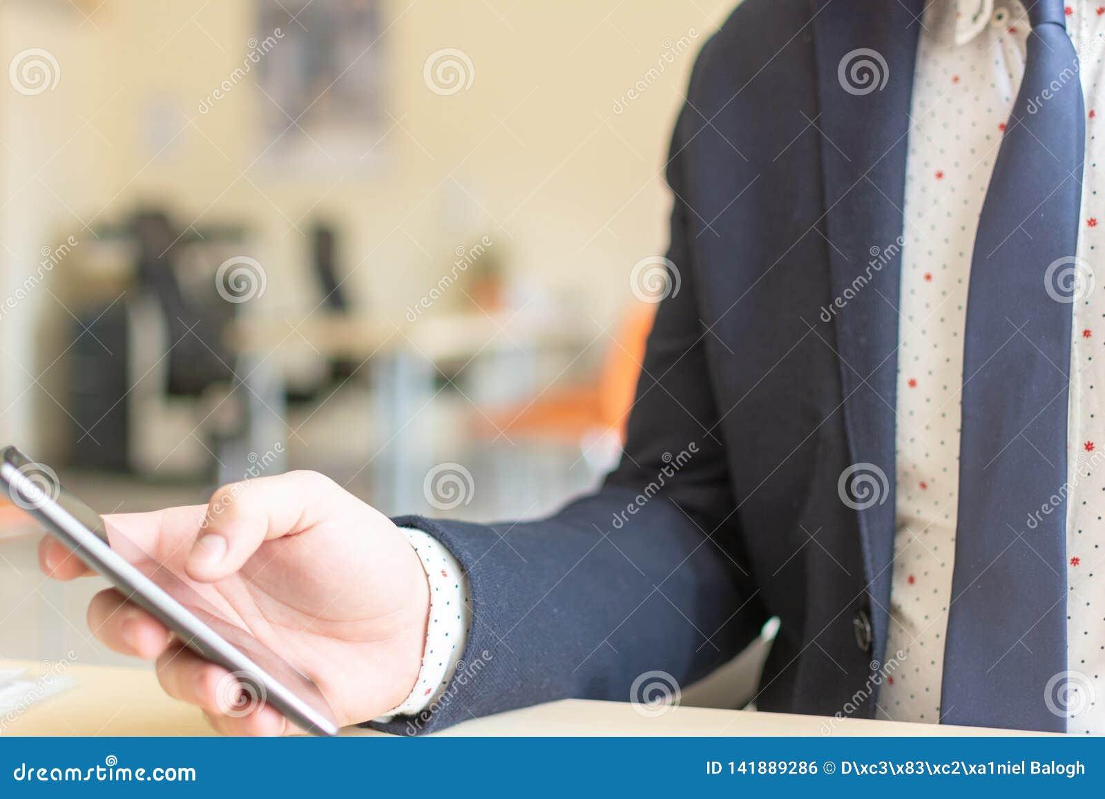 Промежуток времени человека сидя используя мобильный смартфон Уверенный предприниматель работая по телефону