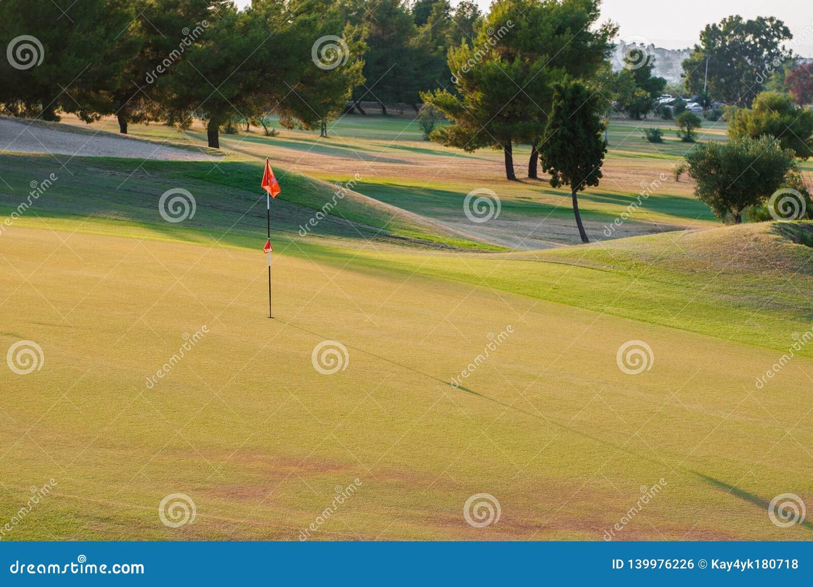 Поле для гольфа на заходе солнца, пустой гольф-клуб